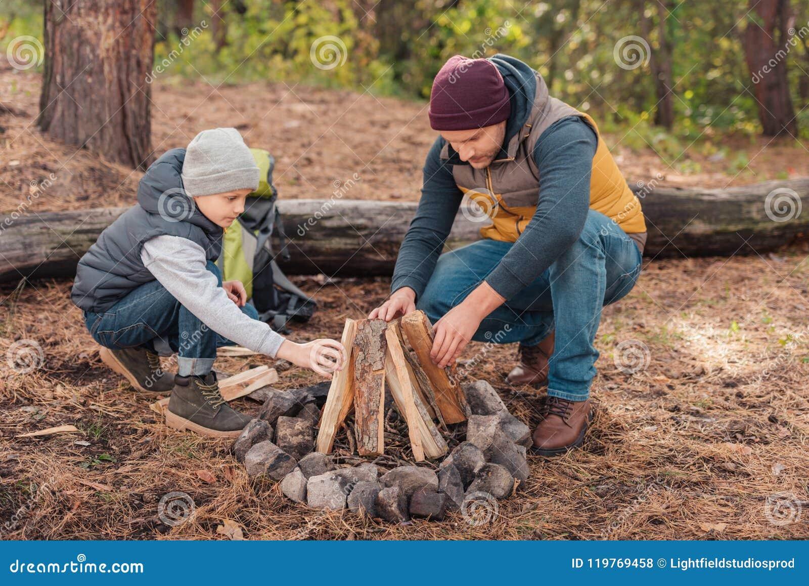 Père et fils rassemblant le bois de chauffage et allumant le feu