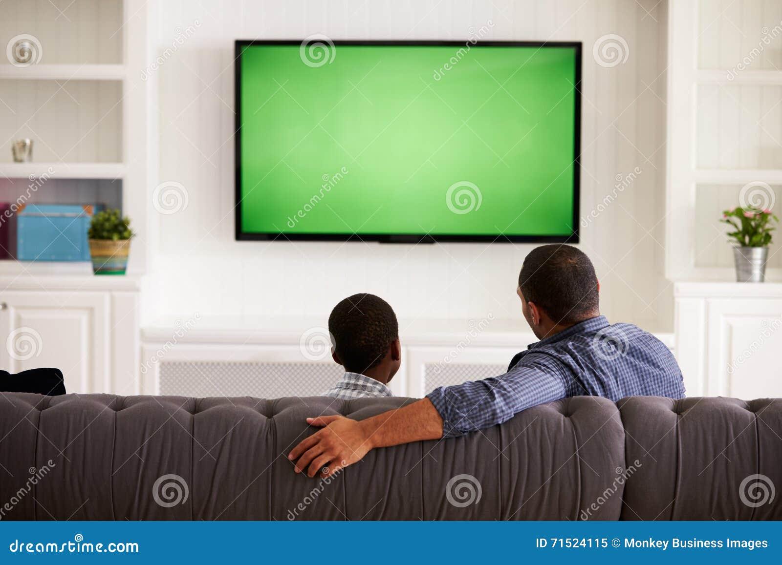Pere Et Fils Regardant La Tv A La Maison Ensemble Vue Arriere Image