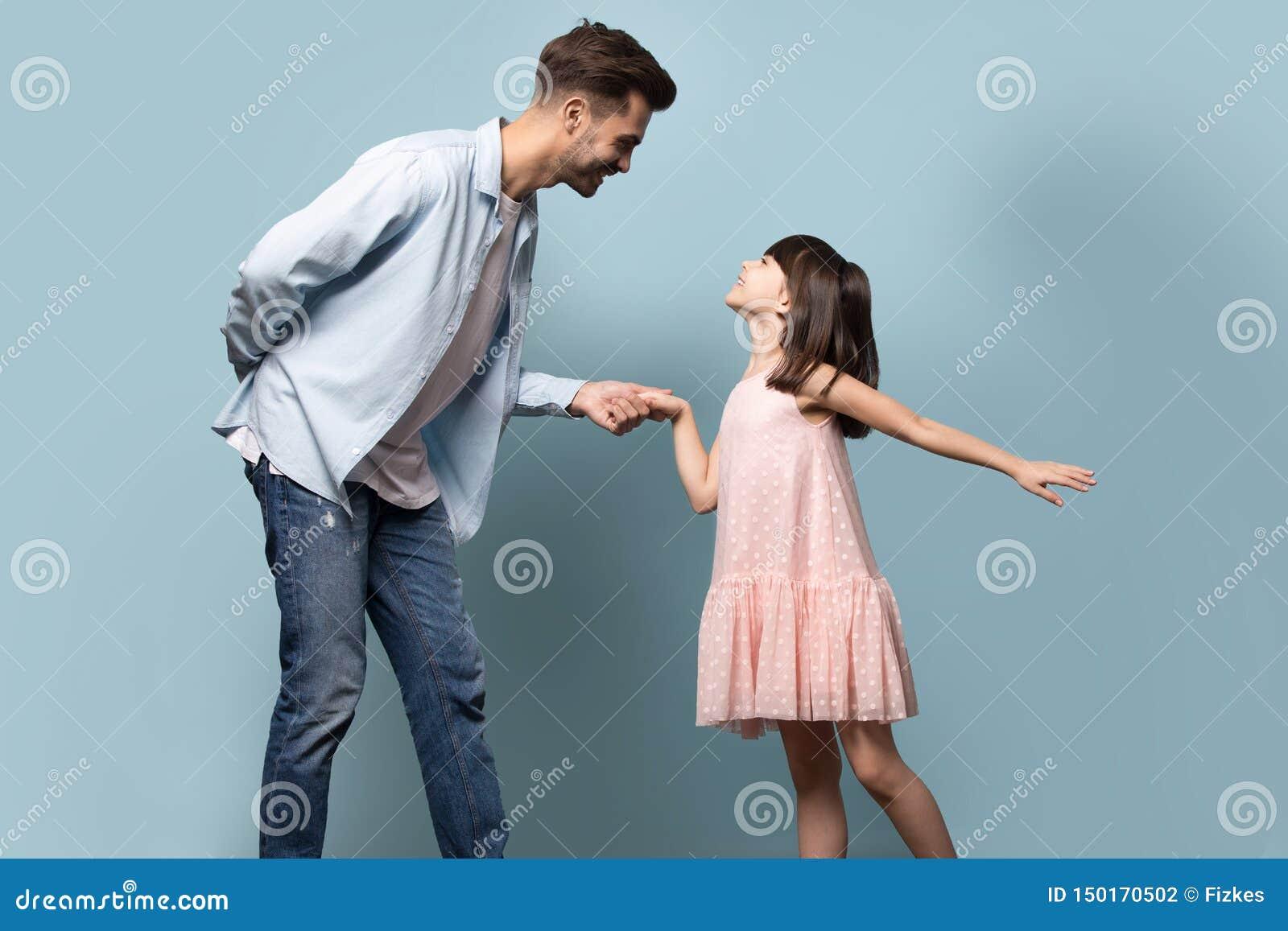Père et peu de fille tenant des mains dansant le tir de valse de studio