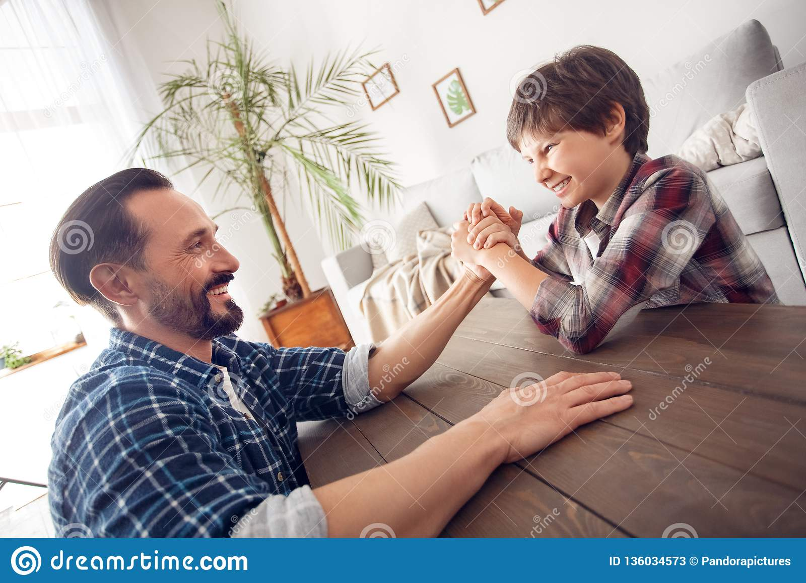Père et peu de fils à la maison s asseyant à la concurrence de bras de fer de table regardant l un l autre joyeux