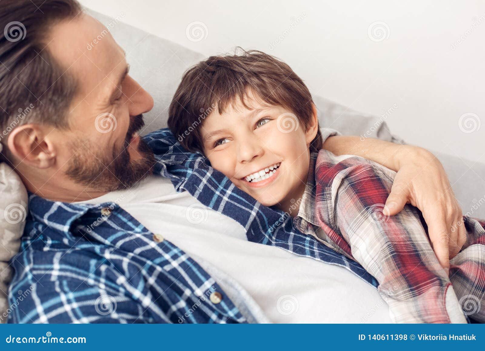 Père et peu de fils à la maison se trouvant sur le papa de sofa étreignant le garçon souriant regardant de côté le plan rapproché