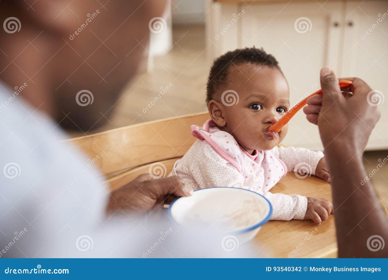 Père Feeding Baby Daughter dans la chaise d arbitre