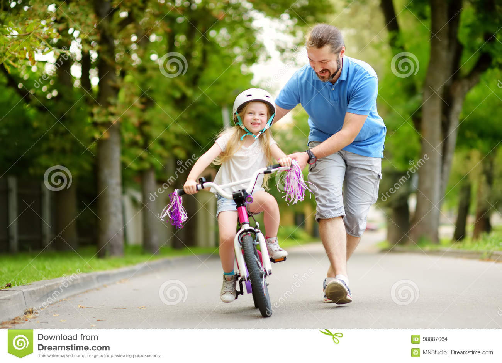 Père heureux enseignant sa petite fille à monter une bicyclette Enfant apprenant à monter un vélo
