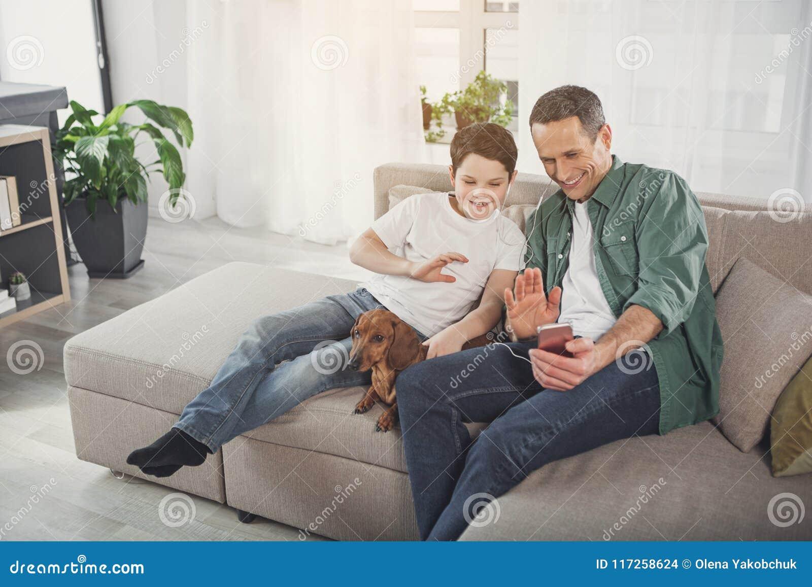 Père heureux et fils ayant la communication d Internet à la maison