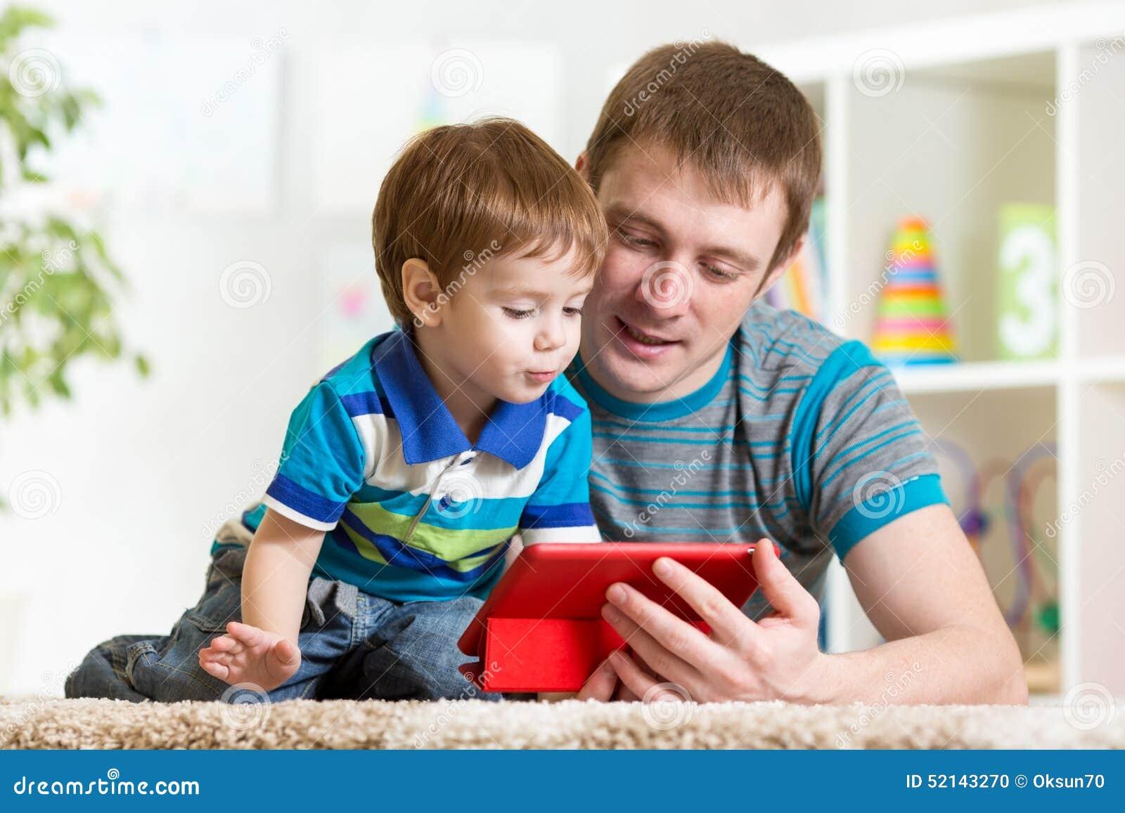 Père heureux et son enfant avec le PC de comprimé