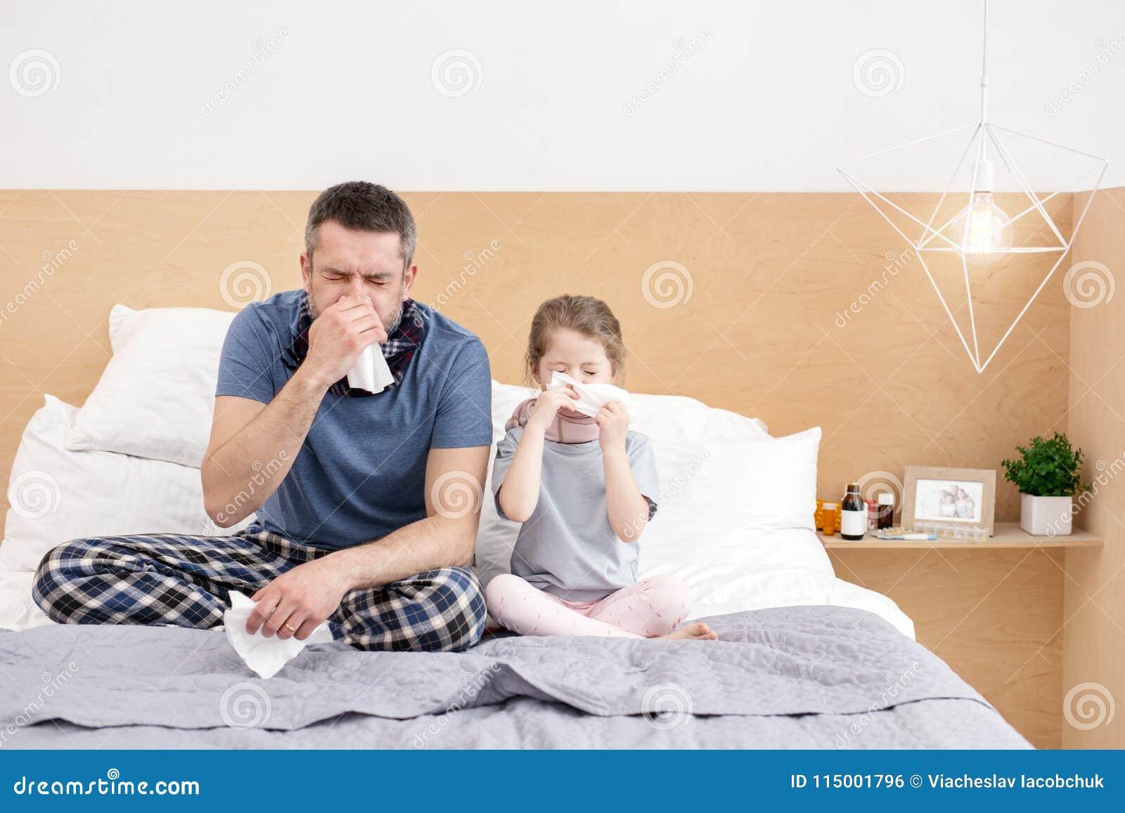Père malade et fille soufflant leurs nez