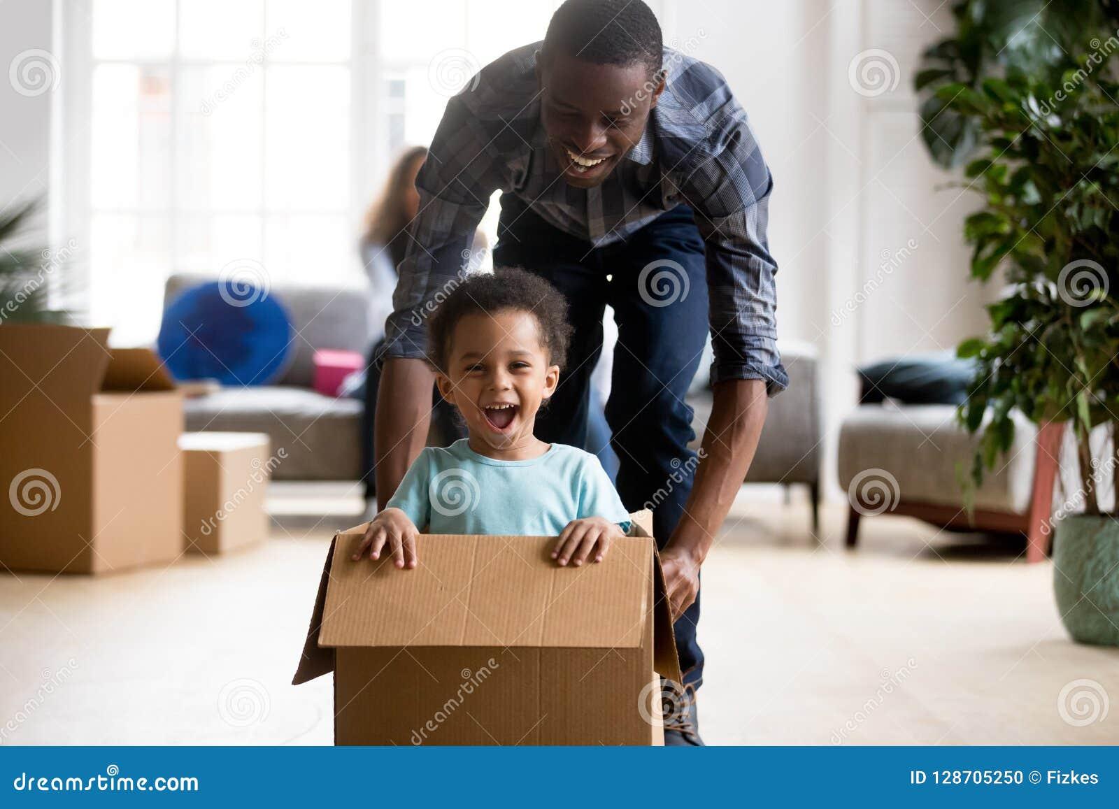 Père noir et fils jouant avec la boîte à la maison