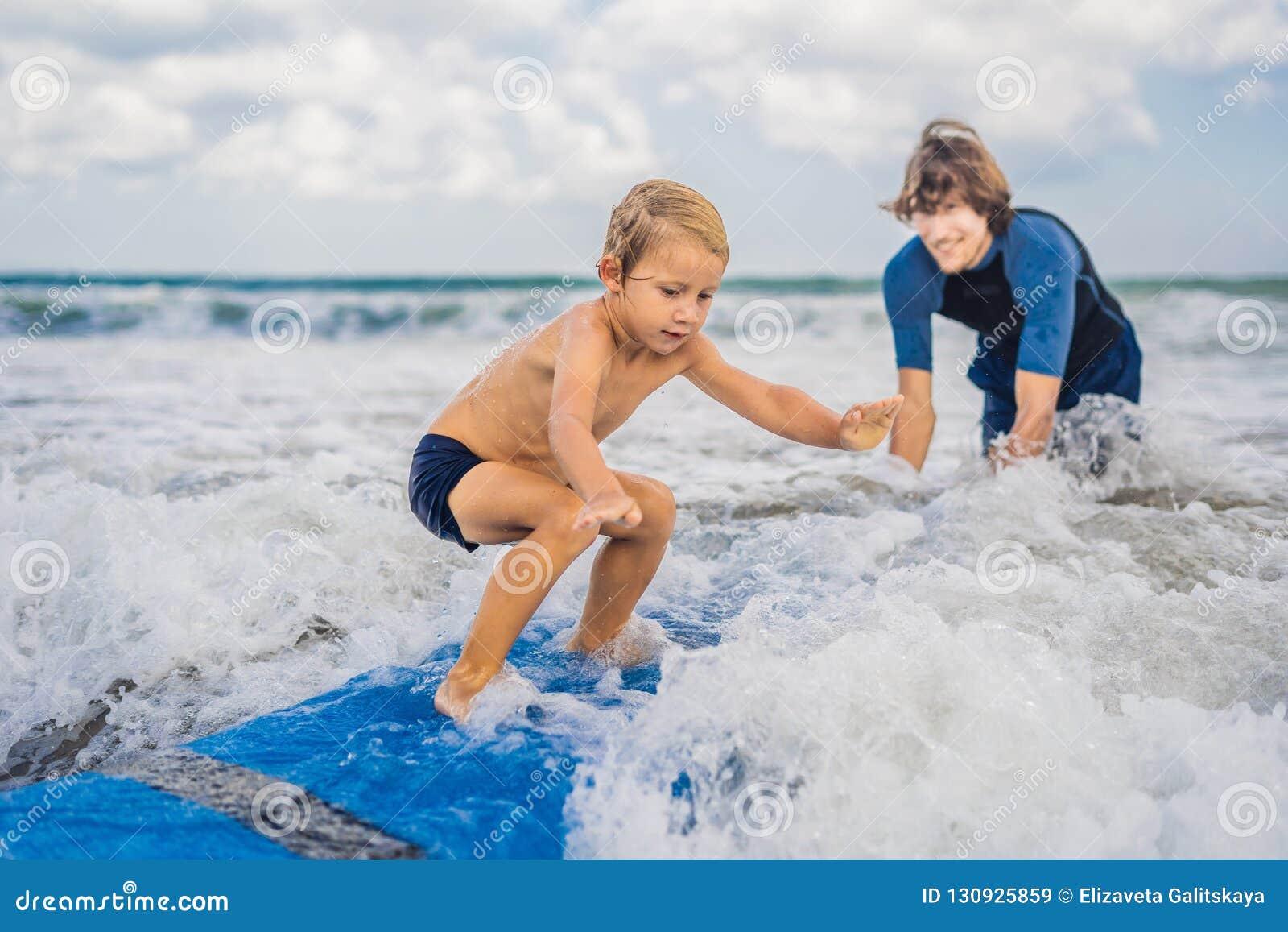 Père ou instructeur enseignant à ses 4 le fils an comment surfer dedans