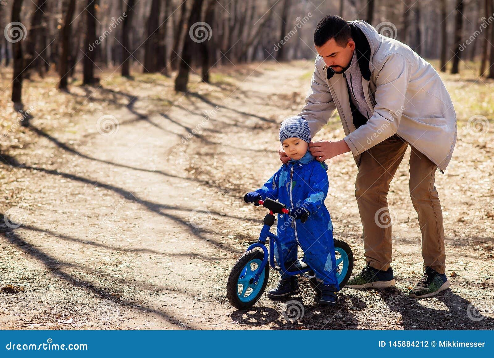 Père plaçant un chapeau à son fils d enfant en bas âge dans la salopette bleue en parc L enfant s assied sur un vélo bleu d équil