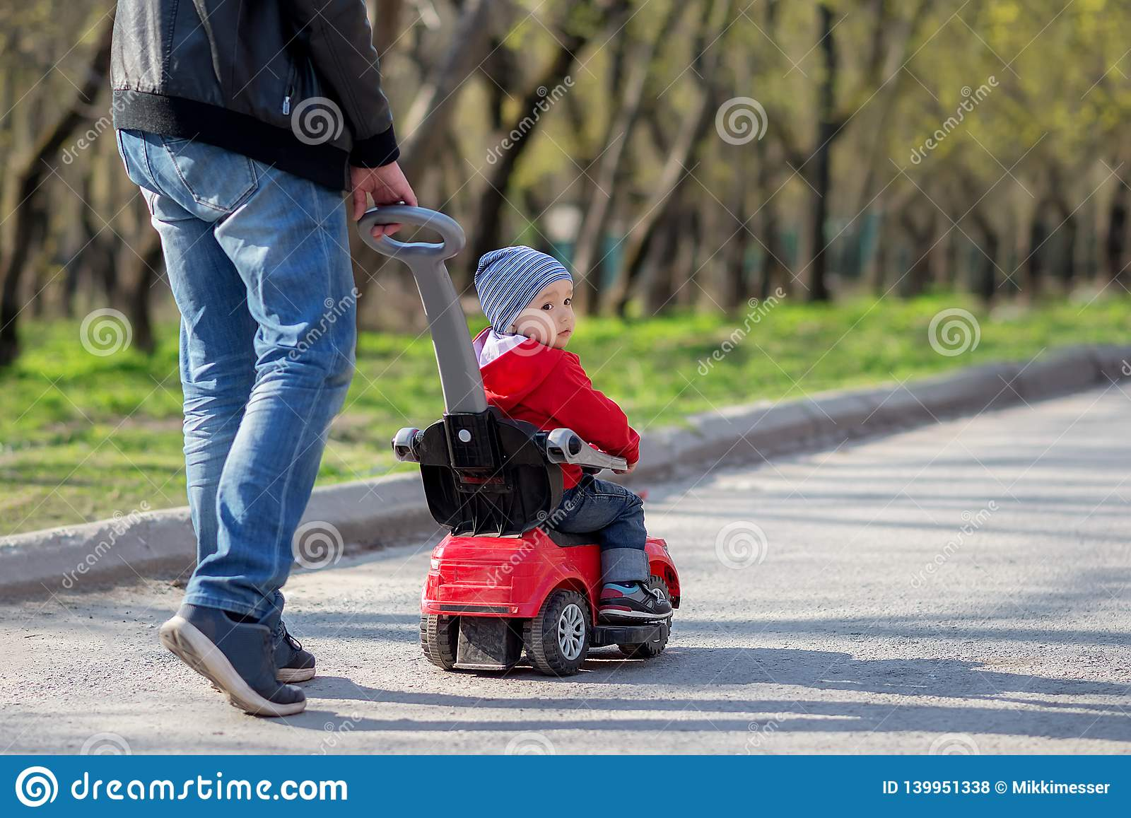 Père poussant une voiture rouge de poussée avec son fils d enfant en bas âge la montant sur une promenade de ressort Promenade de