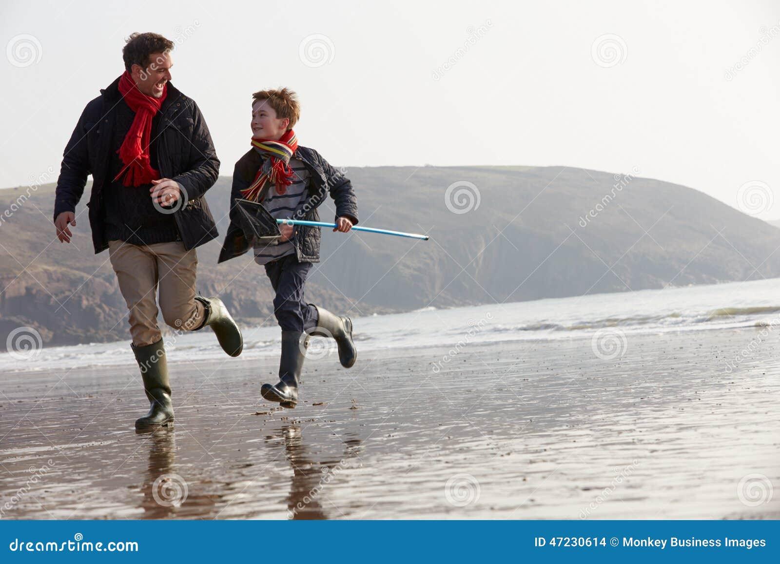 Père And Son Running sur la plage d hiver avec le filet de pêche