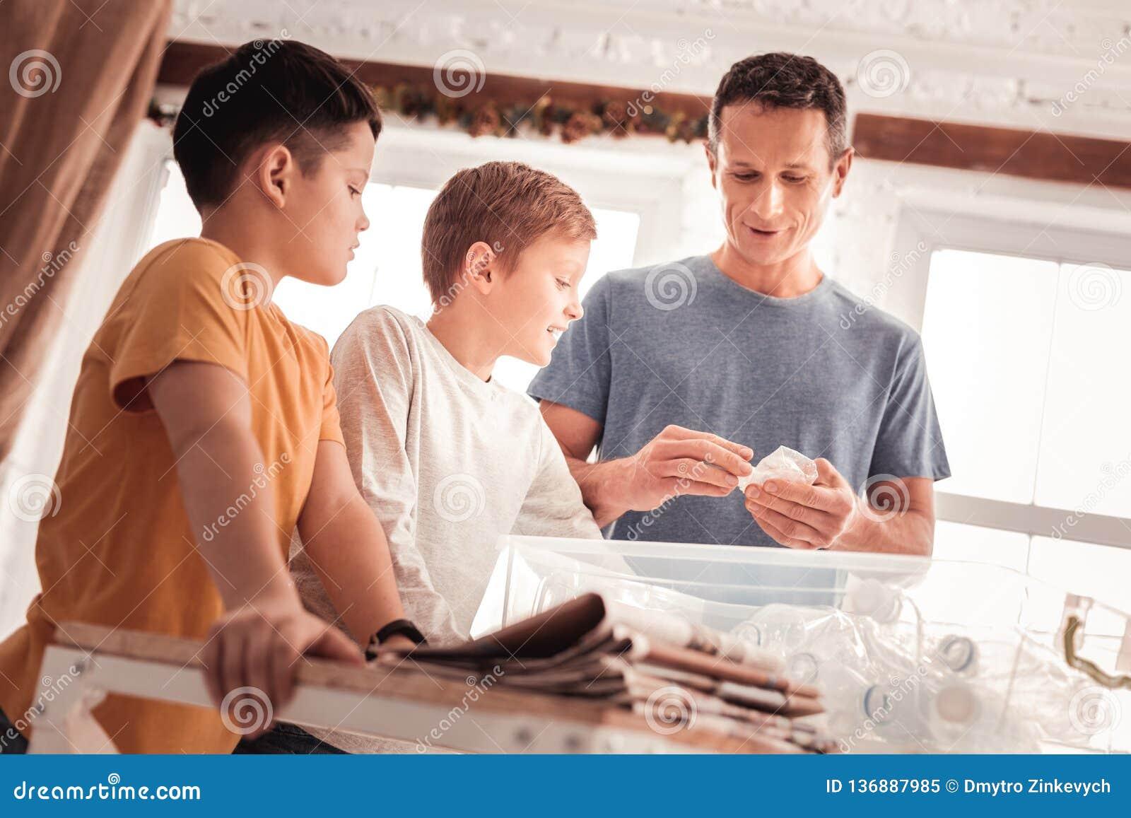Père utilisant la chemise bleue indiquant ses fils au sujet du tri de déchets