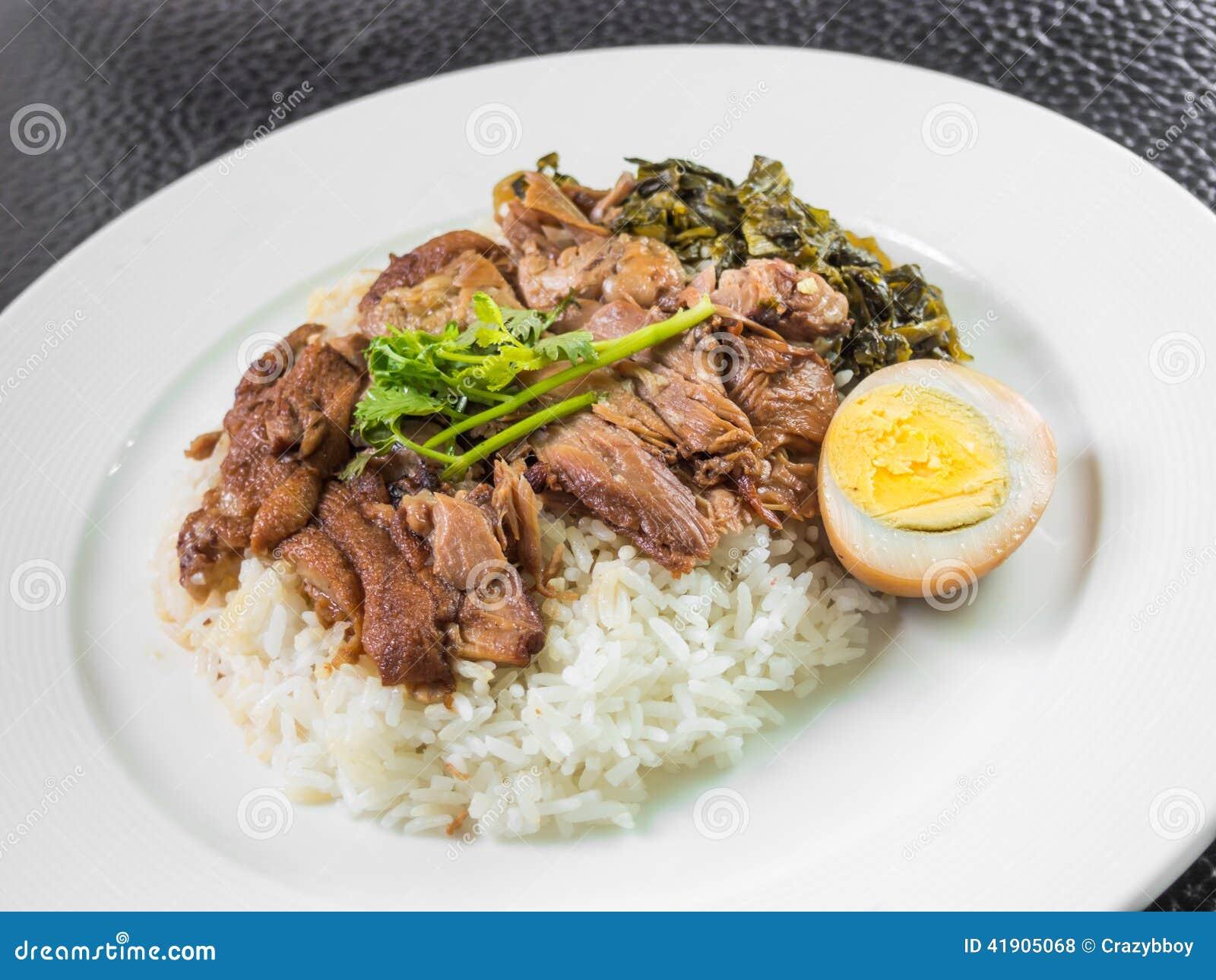 Pé cozido da carne de porco no arroz com ovo cozido e conserva