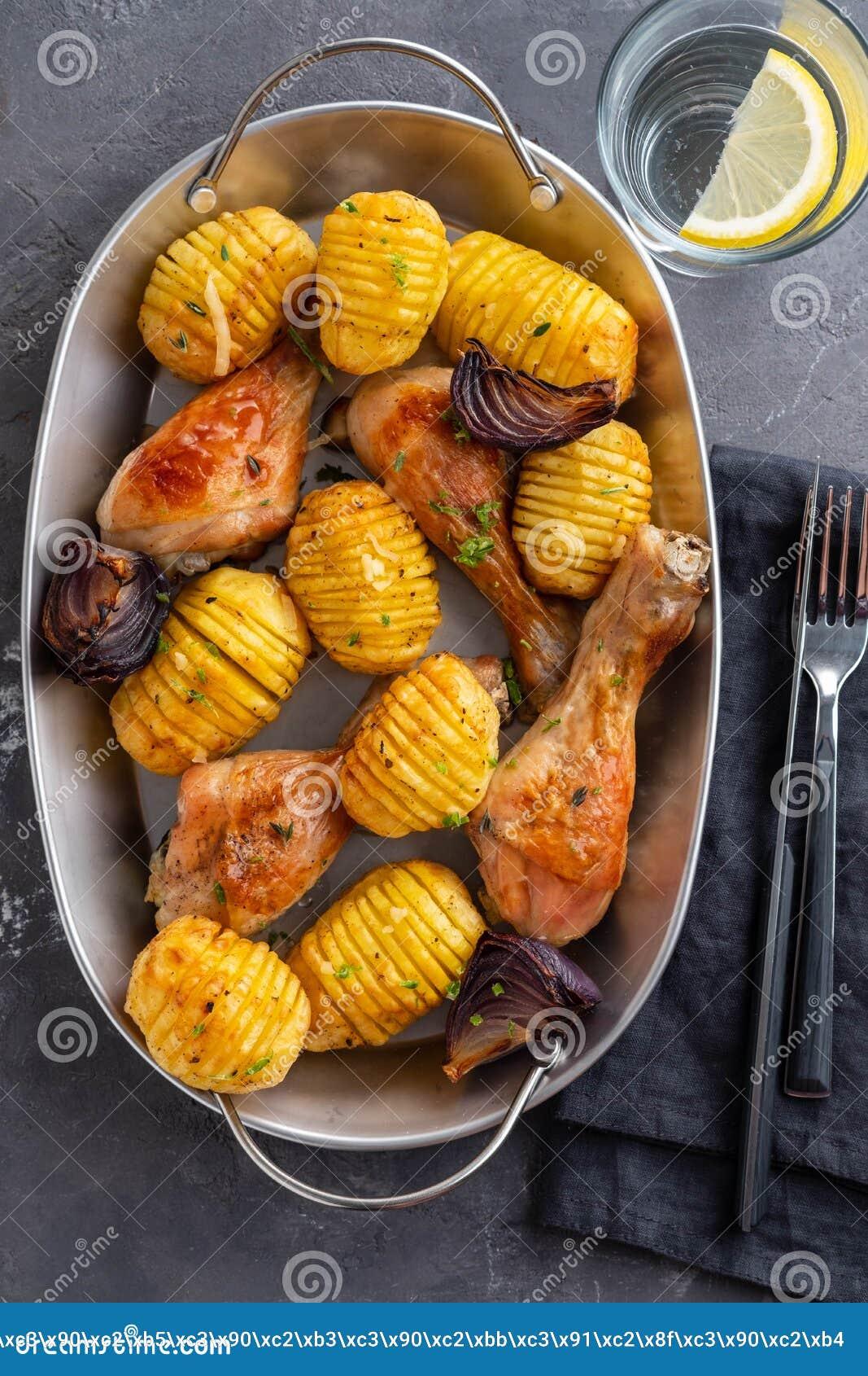 Pé de galinha assado com batatas e os vegetais fervidos no fundo preto Copie o espaço Vista superior