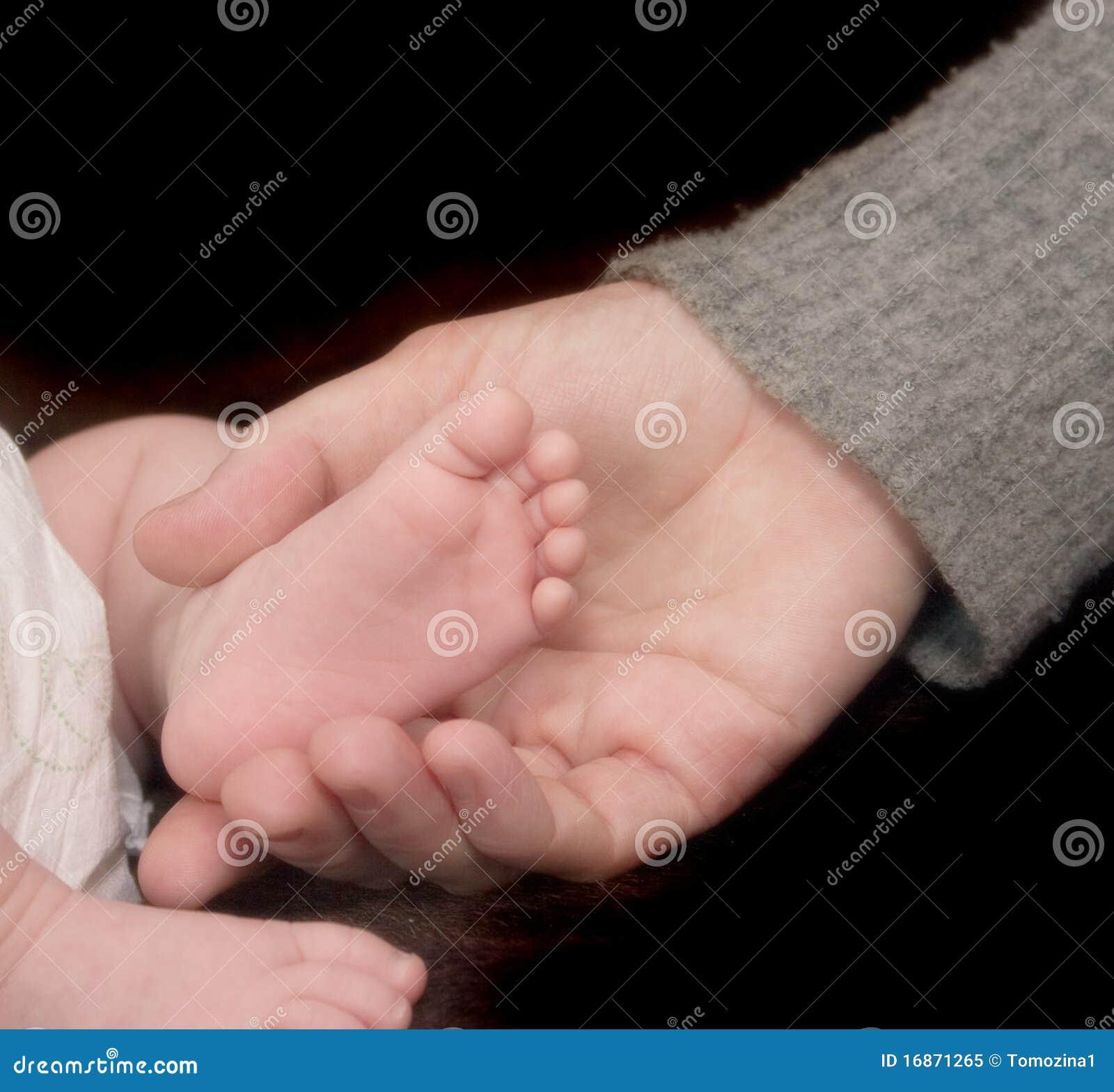 Pé do bebê em uma mão do adulto