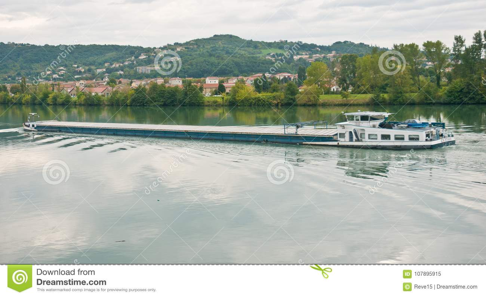 Péniche de rivière maudissant sur le Rhône un jour nuageux