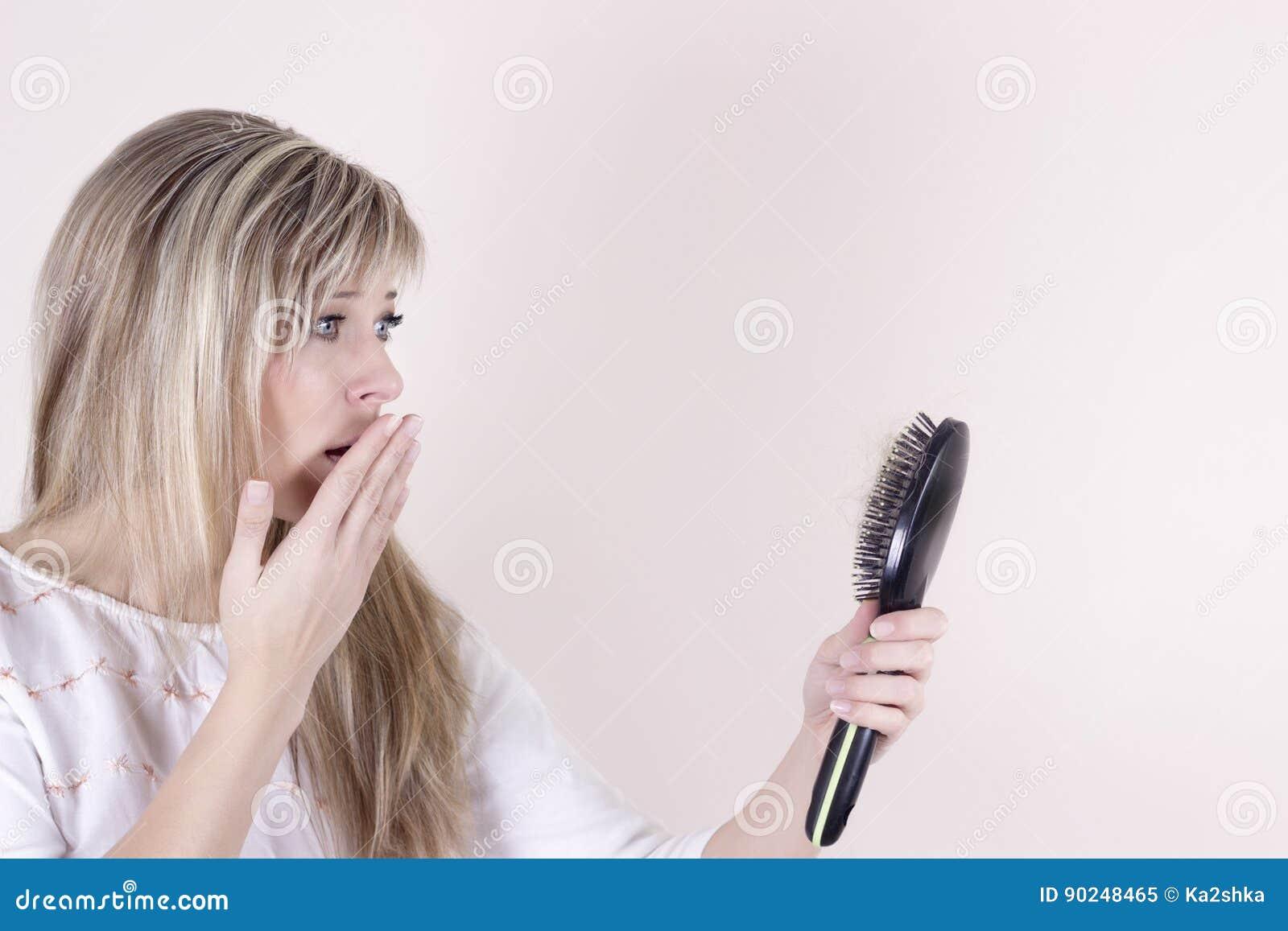 Pérdida de pelo Mujer joven deprimida que mira su cepillo para el pelo y que expresa negatividad