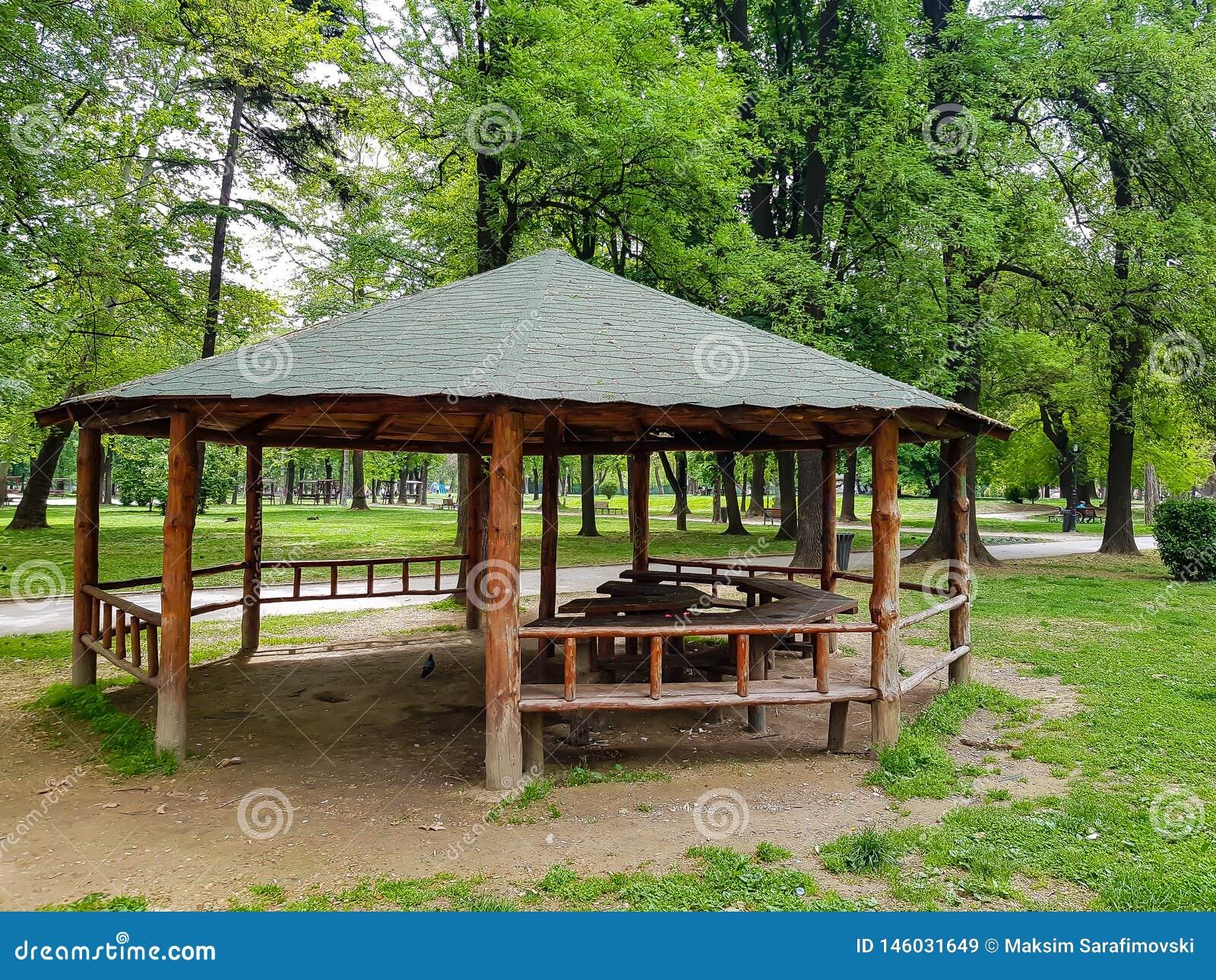 Pérgola de madera con el tejado verde en parque de la ciudad