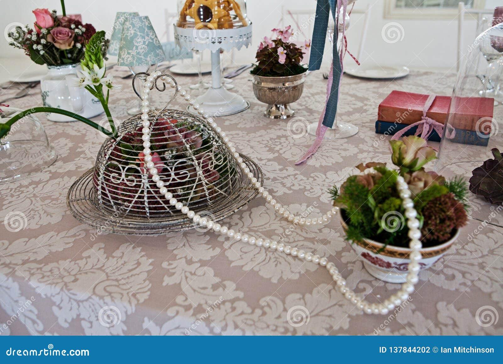 Pérolas e flores elegantes do vintage em um pano de tabela de seda do laço