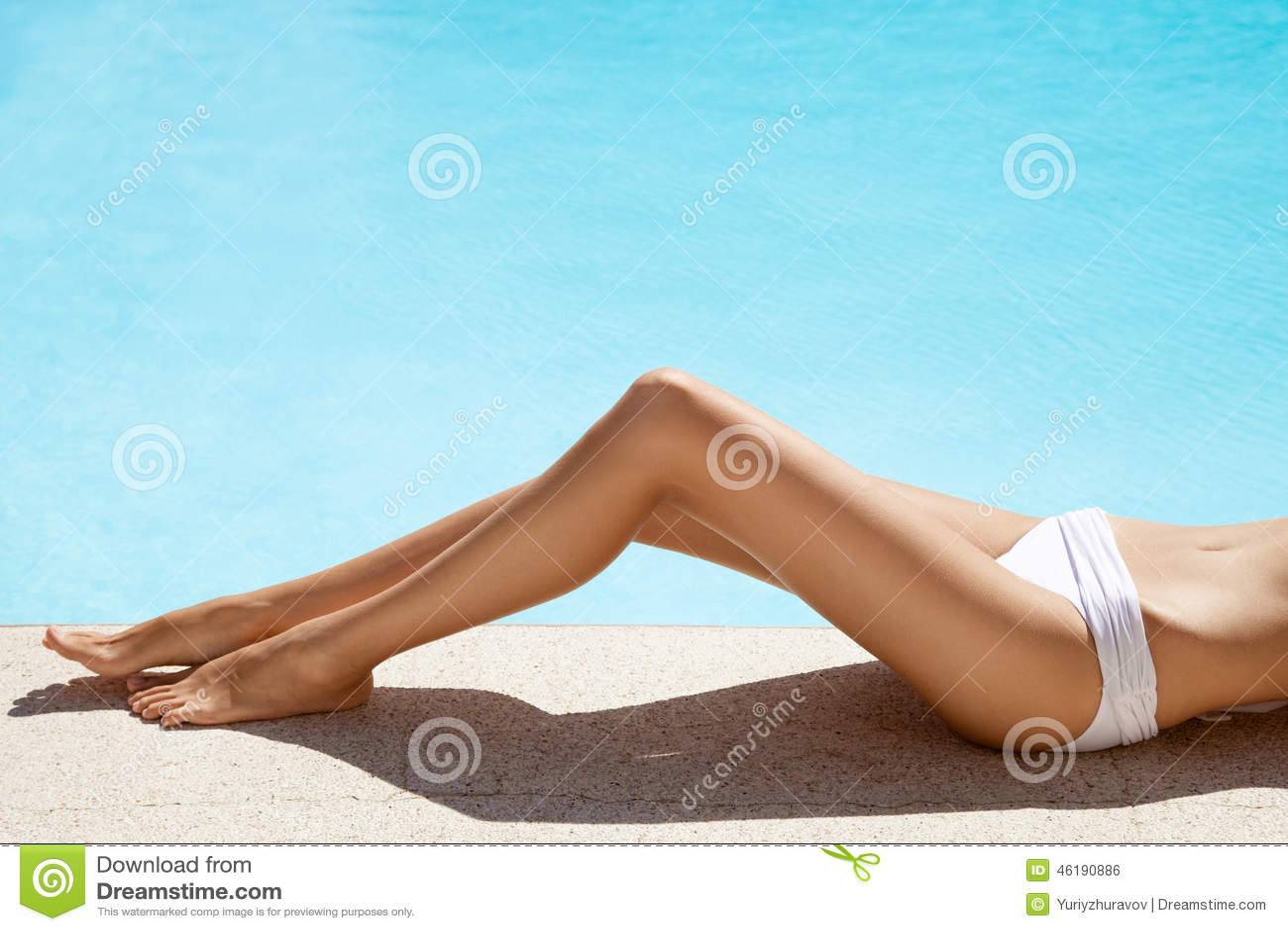 Pés bonitos da mulher perto da piscina