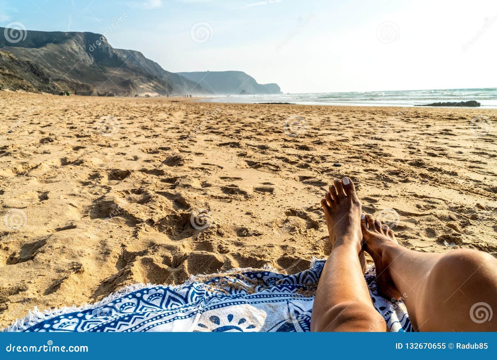 Pés bronzeados da mulher na praia
