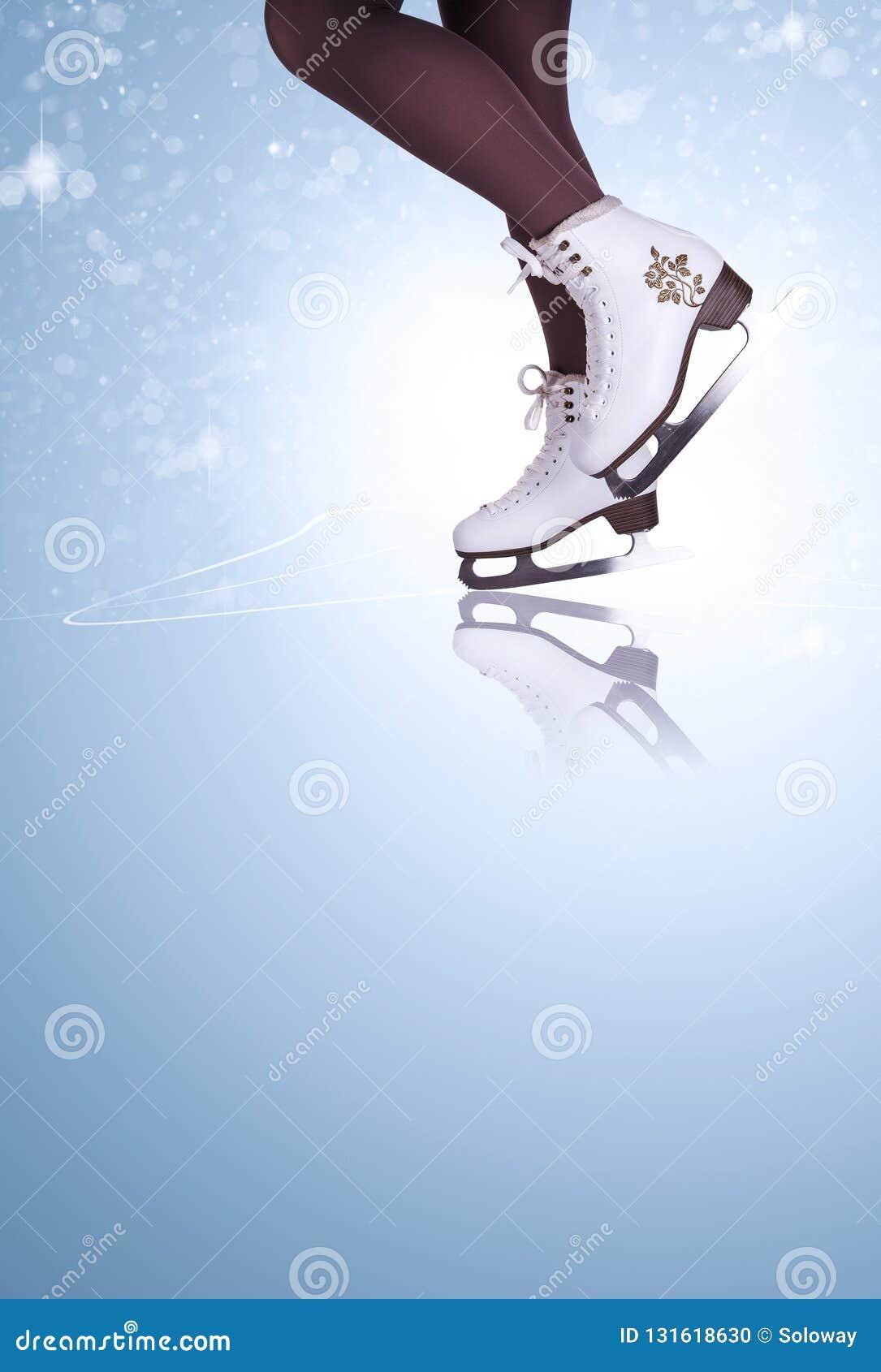 Pés da mulher em botas da patinagem no gelo