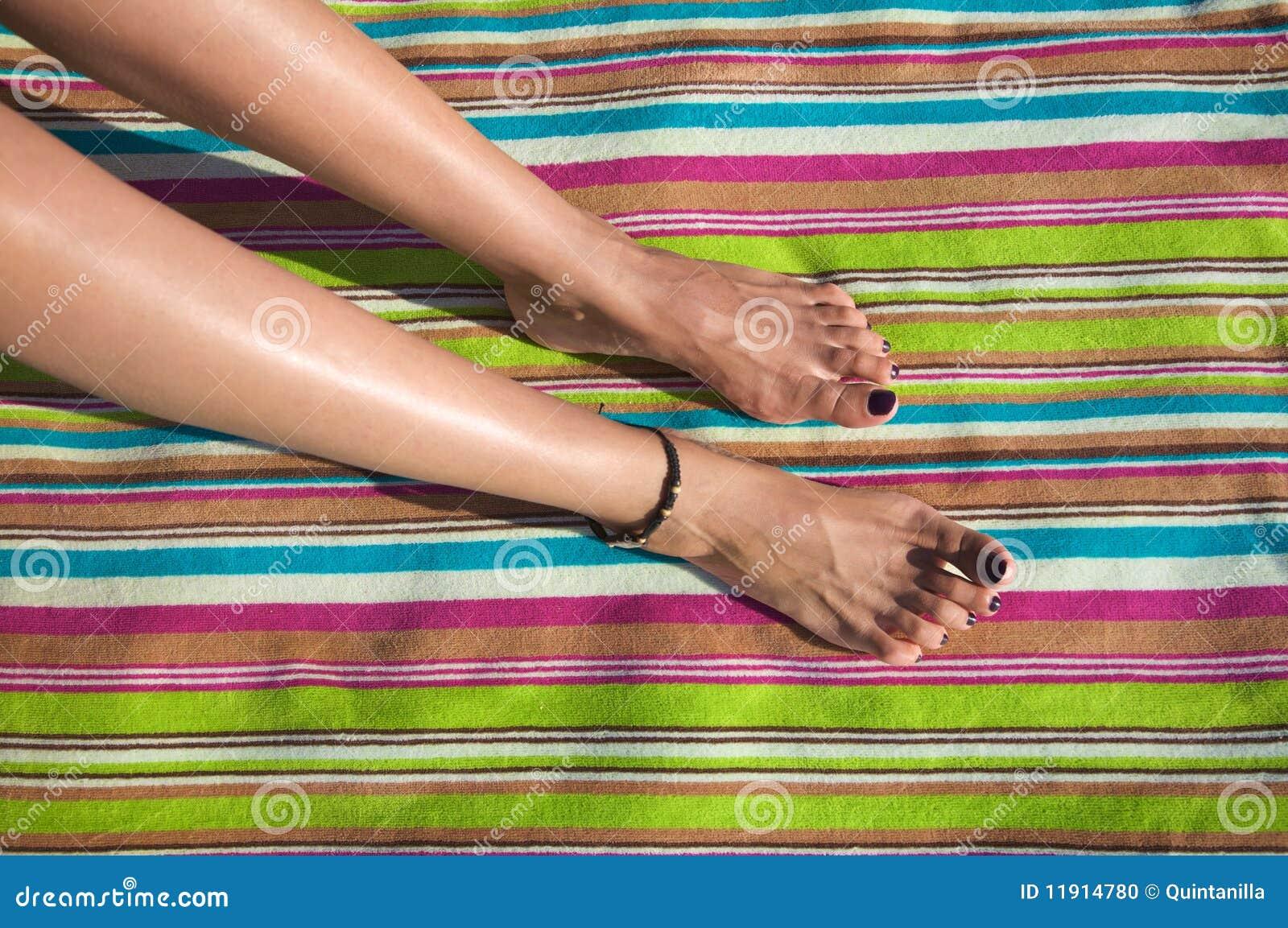 Pés da mulher em toalha listrada