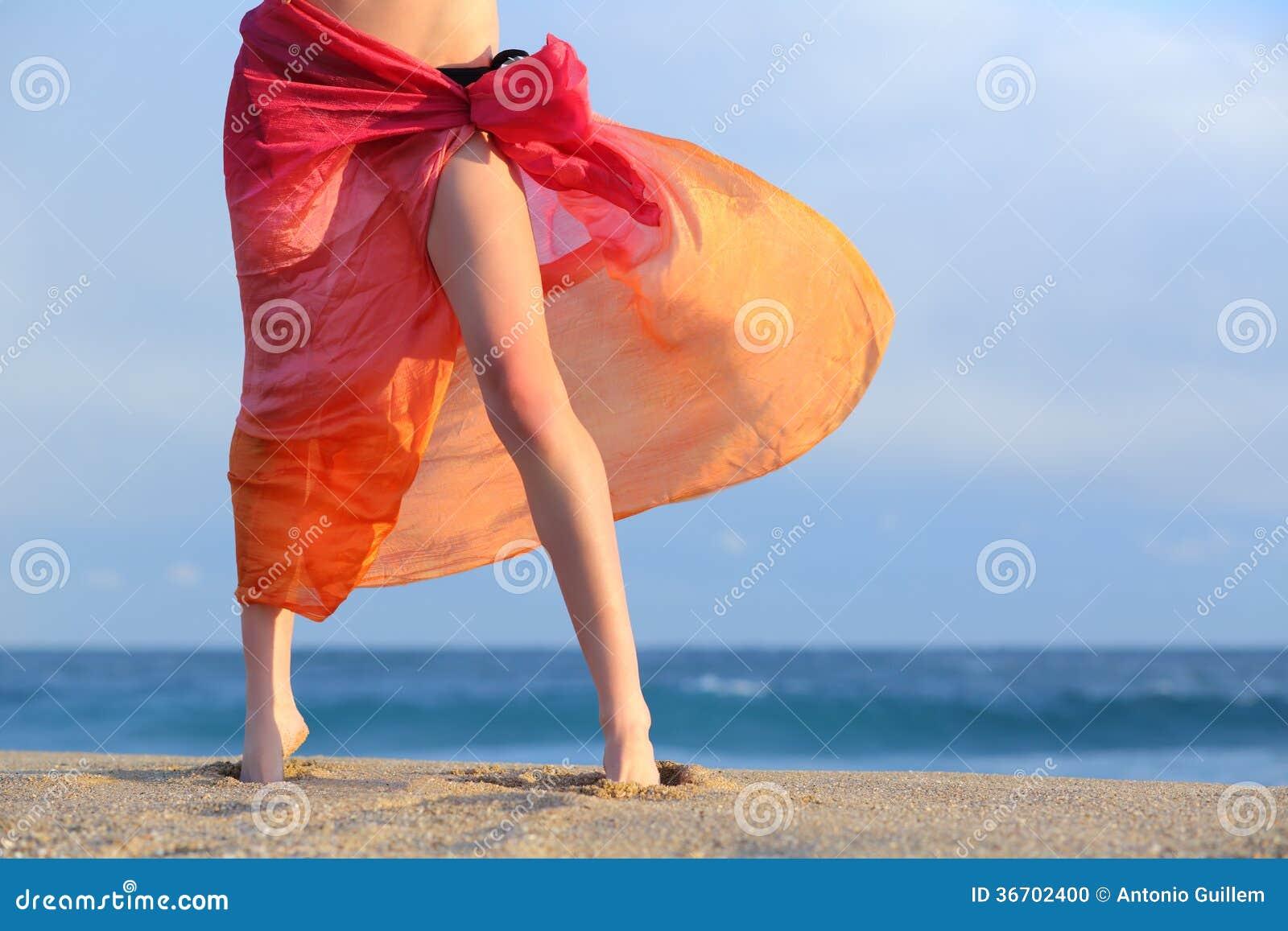 Pés da mulher nas férias que levantam na praia com um pareo
