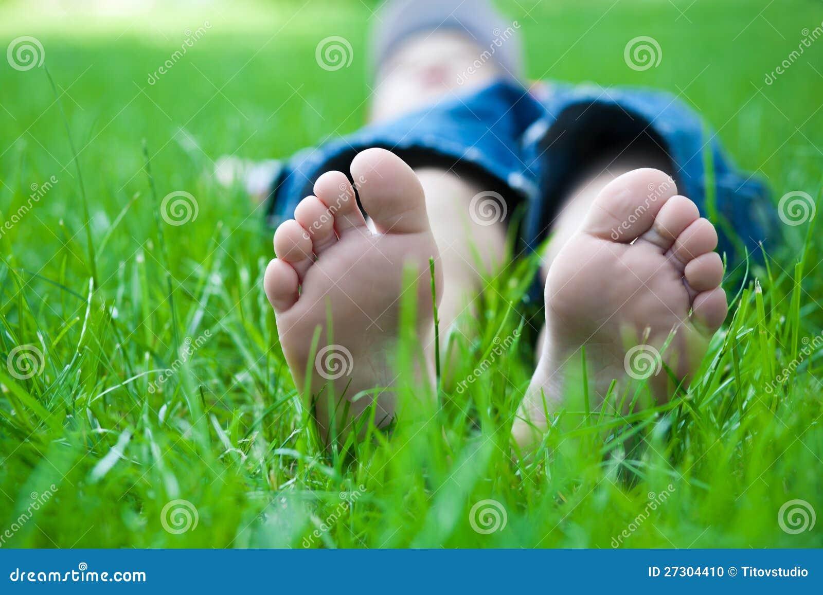 Pés das crianças na grama. piquenique no parque da mola