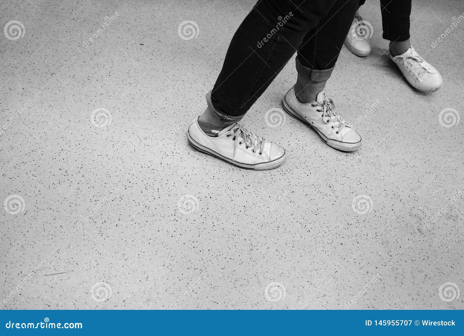 Pés de dois dançarinos nas sapatas brancas