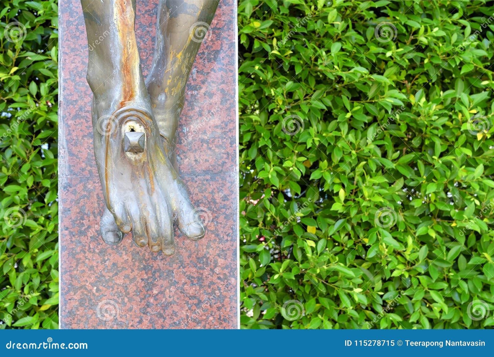 Pés de Jesus Statue com fundo verde da parede das folhas