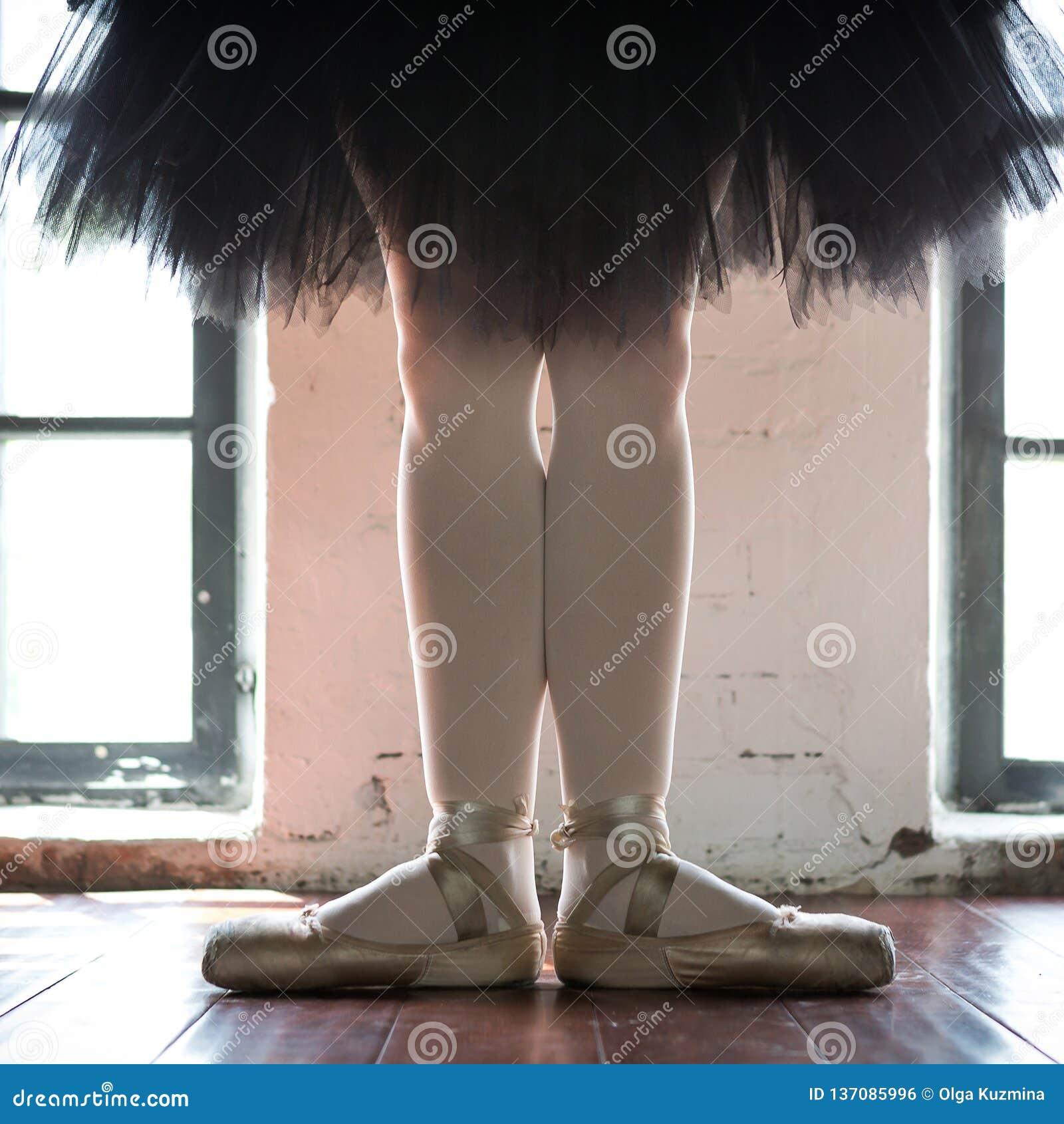 Pés de um close up da bailarina Os pés de uma bailarina no pointe velho Bailarina do ensaio no salão Luz do contorno da janela