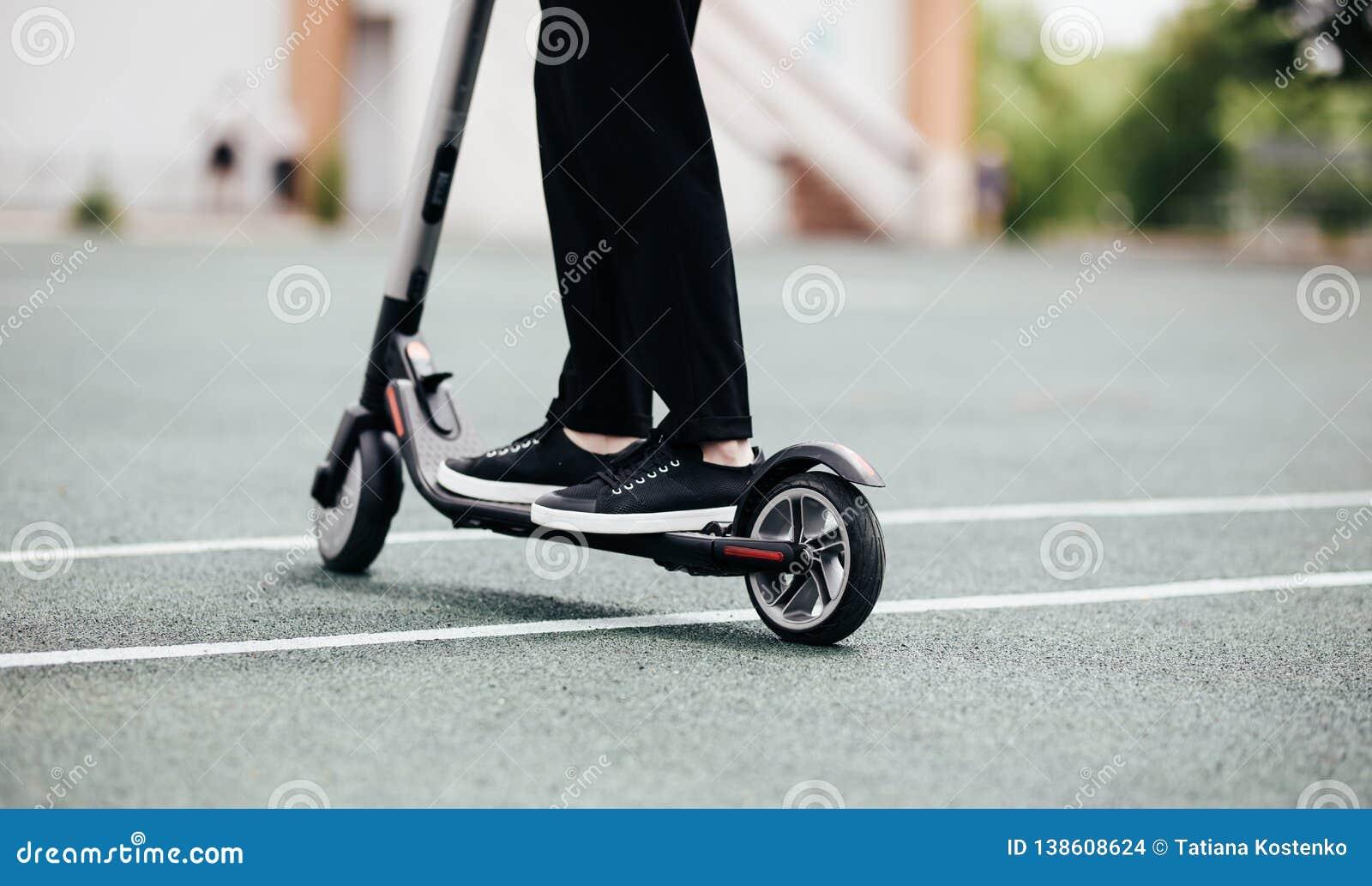 Pés de um homem no suporte à moda do equipamento no  trotinette  elétrico na rua