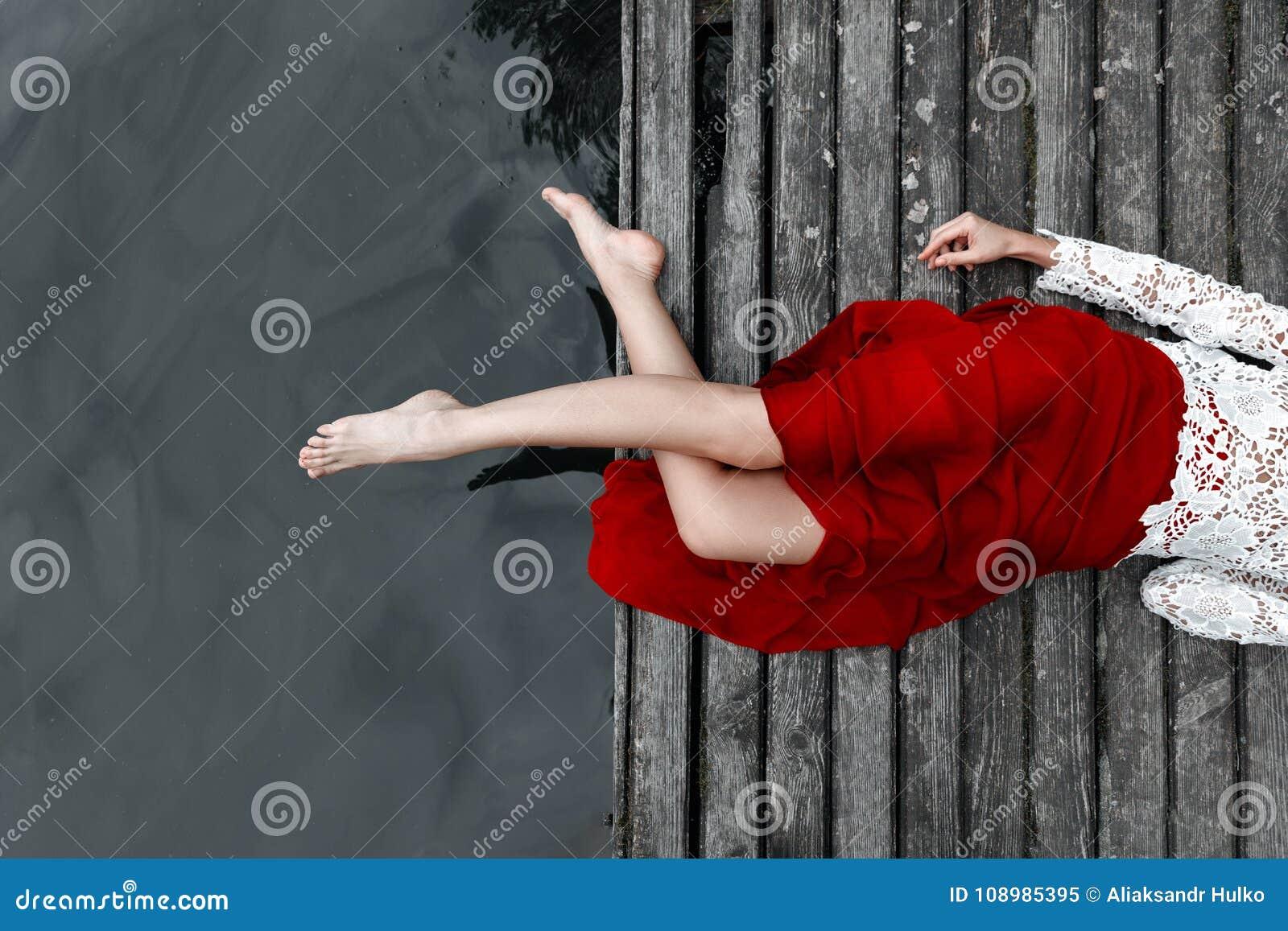 Pés de uma menina em uma saia vermelha em uma ponte