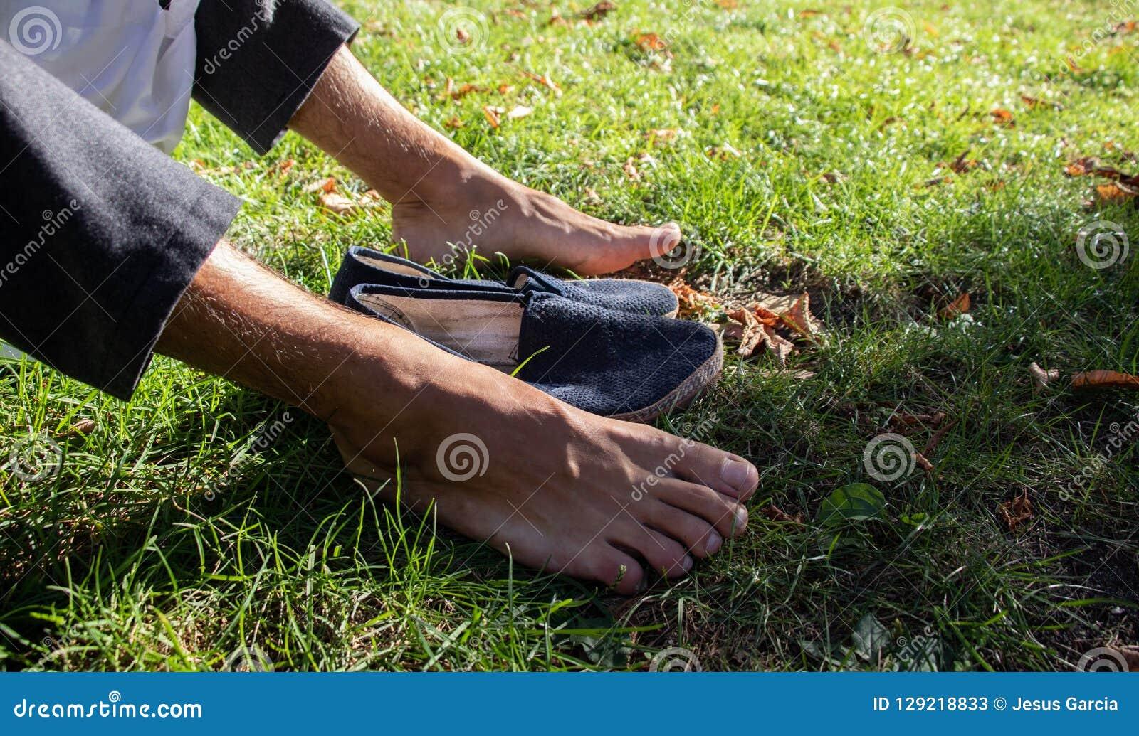 Pés desencapados na grama com sapatas azuis