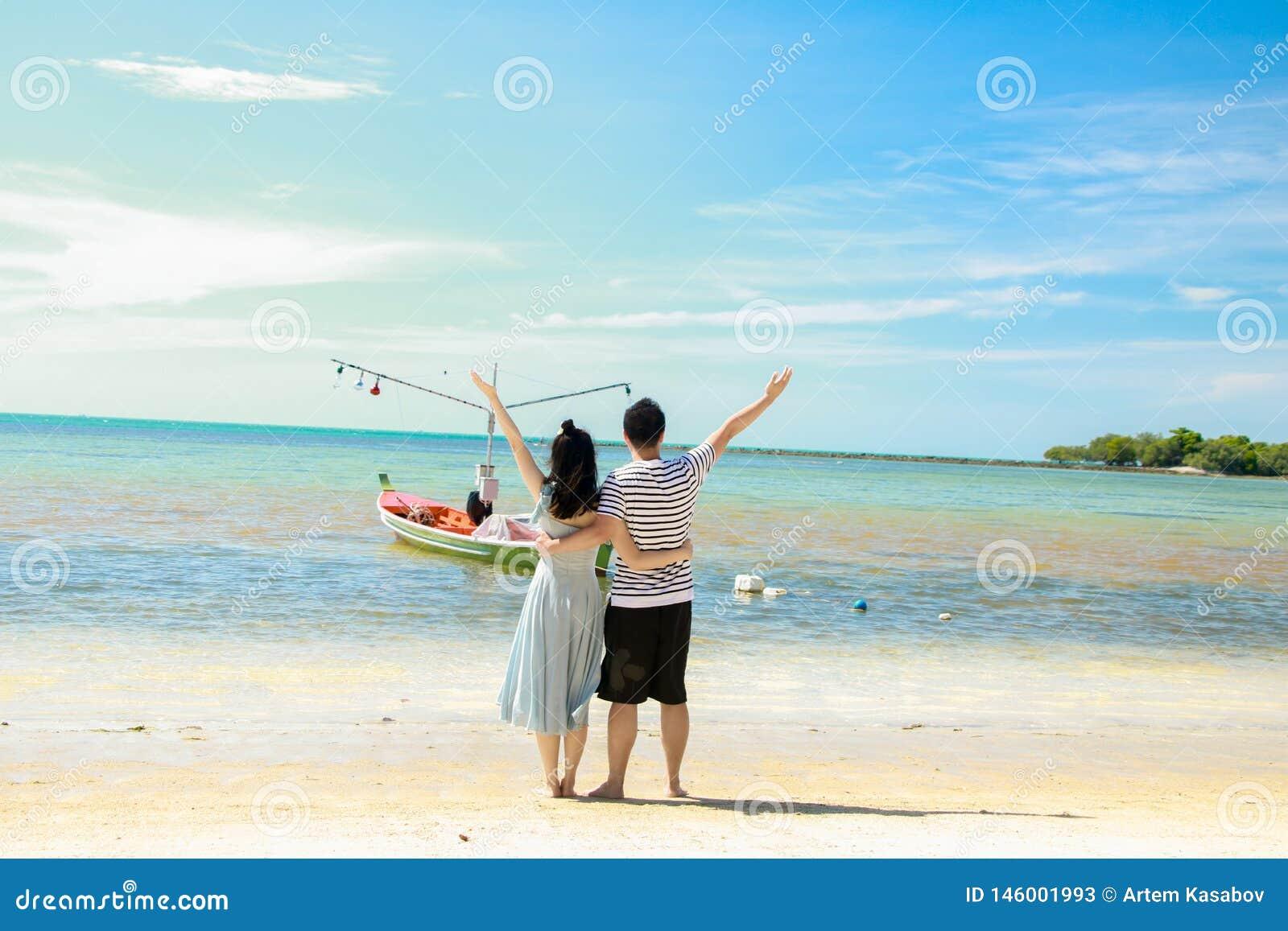 Pés dos pares no beachCouple que olha a viagem mar-doce para dois