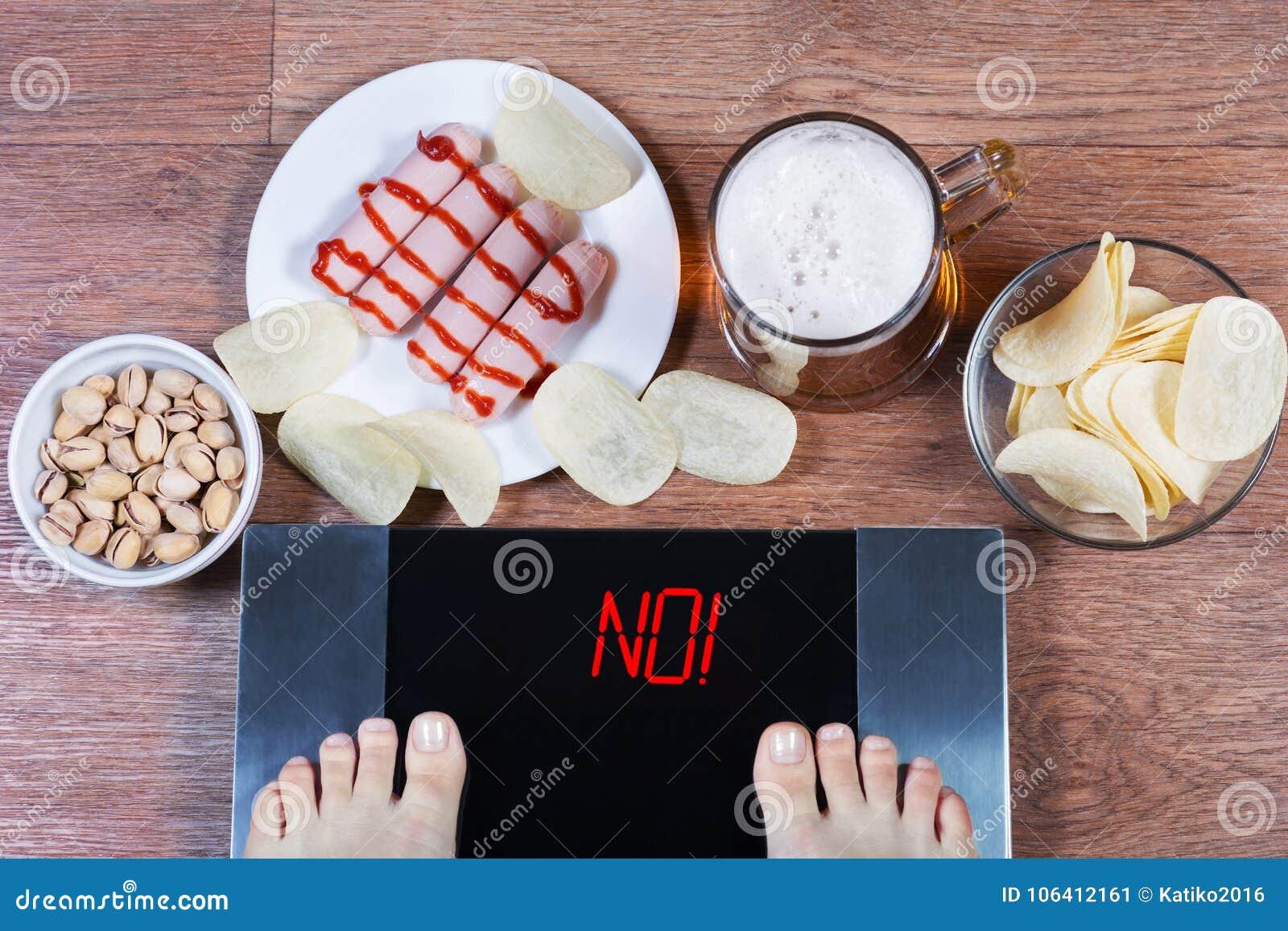 Pés fêmeas em escalas digitais com palavra não na tela Cerveja e placas com salsichas da comida lixo, microplaquetas de batata, p