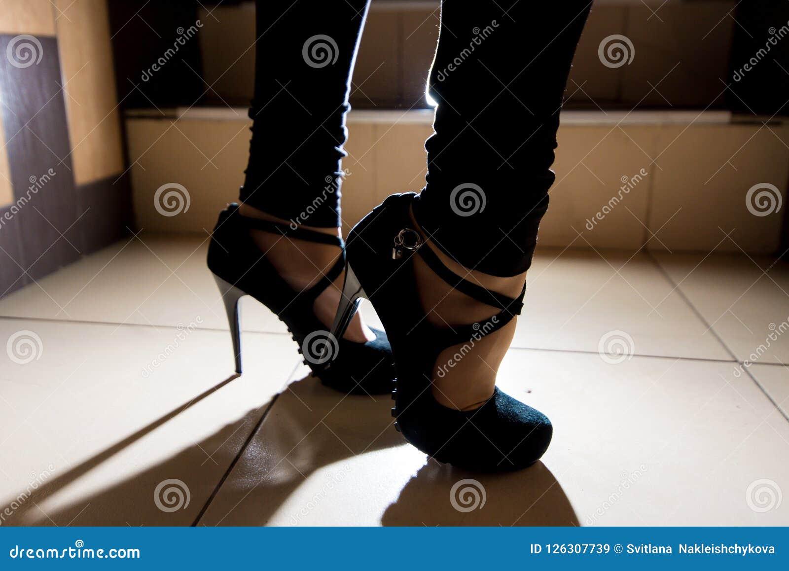 Pés fêmeas em sapatas alto-colocadas saltos preto
