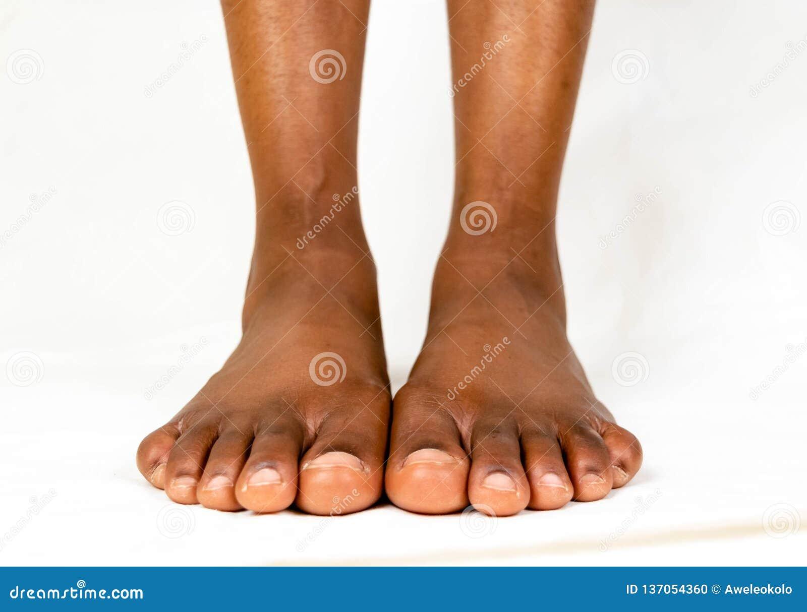Pés lisos fêmeas pretos bonitos com pele lisa Bebê saudável do pé da mulher afro-americano Pés do despido do bebê isolados no whi