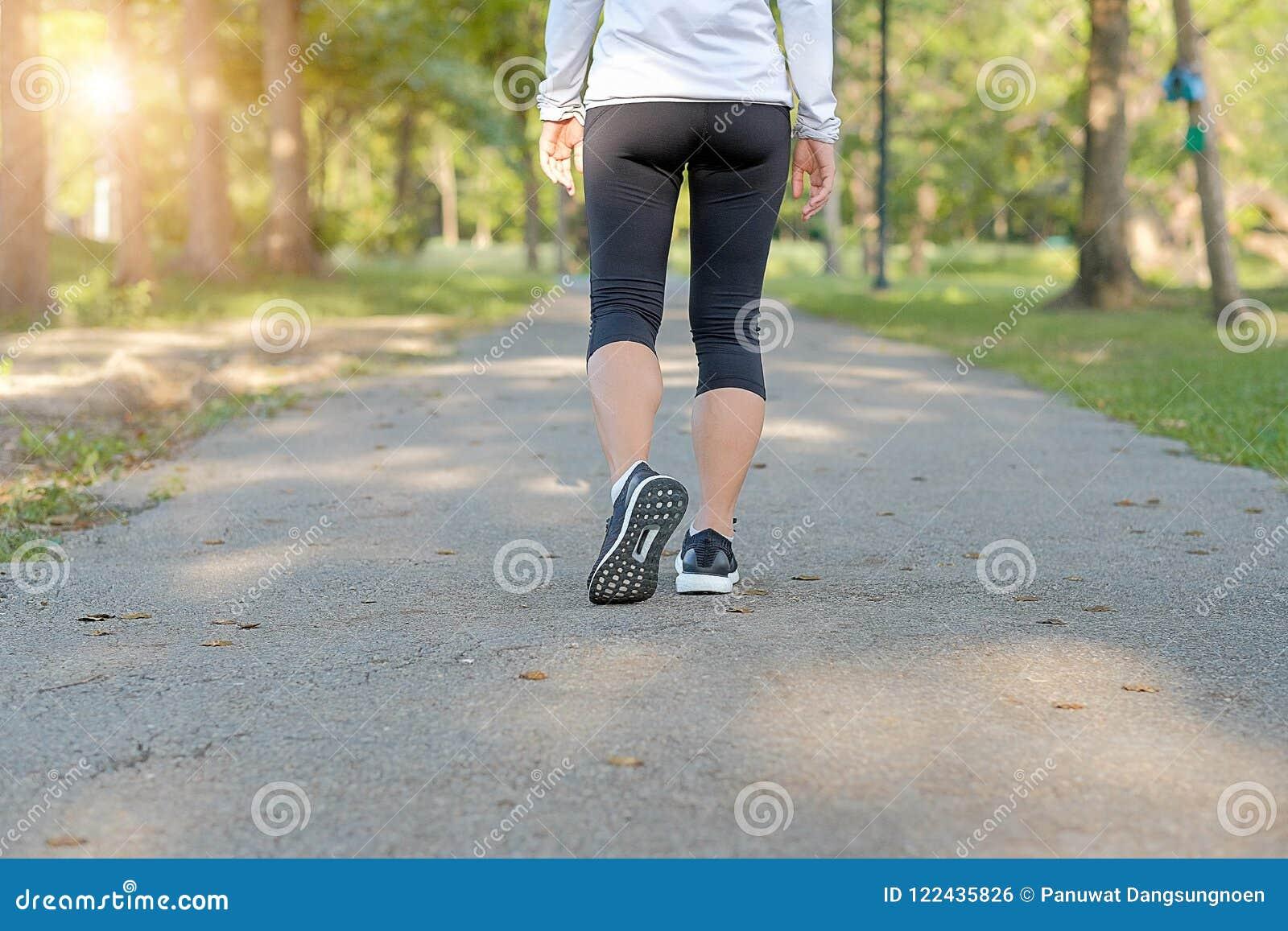 Pés novos da mulher da aptidão que andam no parque exterior, no corredor fêmea que correm na estrada fora, em movimentar-se do at