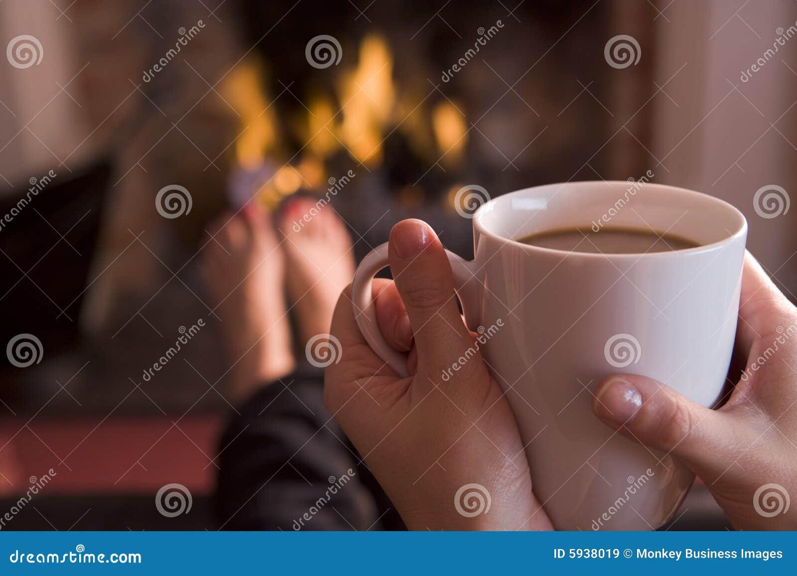 Pés que aquecem-se em uma chaminé com café