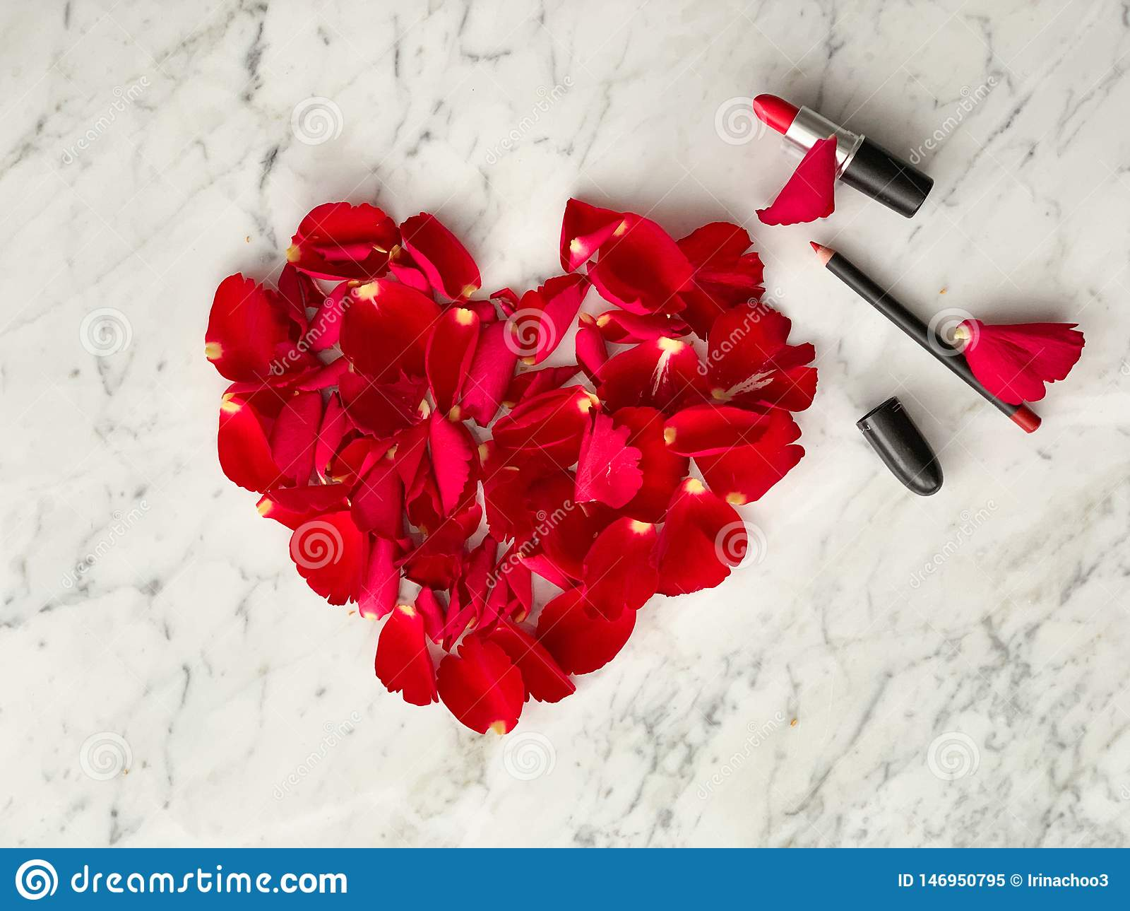 Pétales de rose rouges dans la forme de coeur avec le rouge à lèvres rouge sur le fond de table de marbre, vue supérieure Idées d