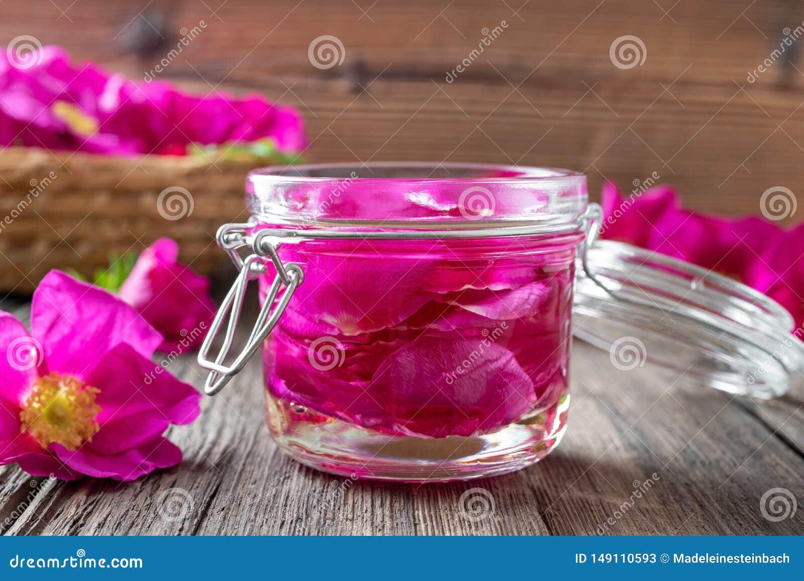 P?tales de rose de Rugosa mac?rant en huile d amandes sur une table