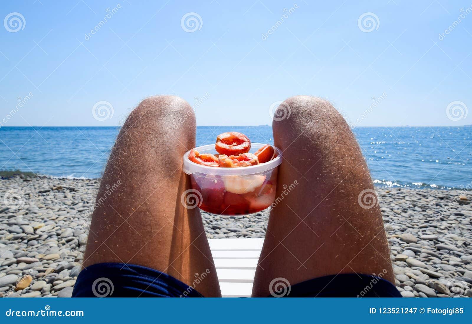 Pêches sur les genoux Pêches épluchées dans une tasse sur les jambes velues masculines Vacances de plage par la mer