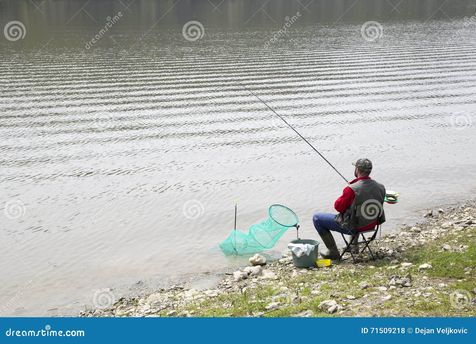 Pêcheur à la ligne s asseyant sur la côte de rivière et les poissons patiemment de attente pour prendre une amorce