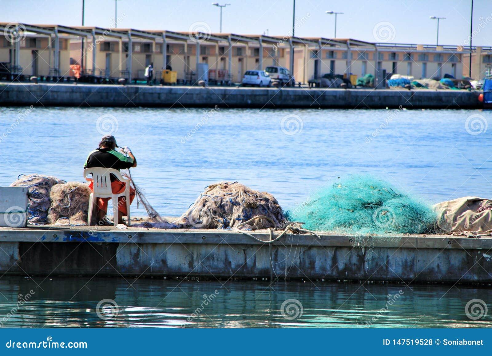 Pêcheur fixant les filets dans le dock de Santa Pola
