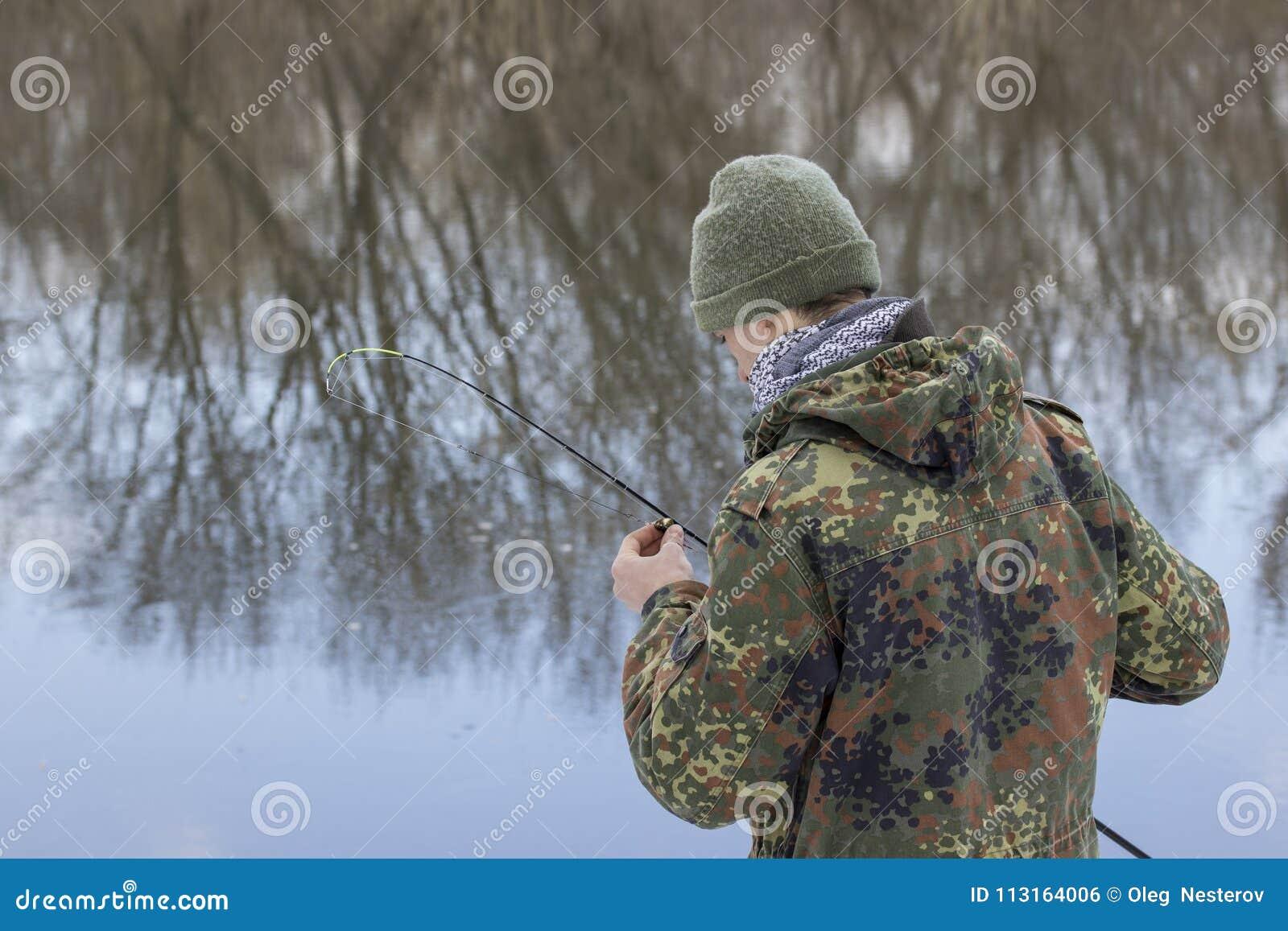 Pêcheur tenant un attrait dans sa main il vérifie l amorce avant la pêche