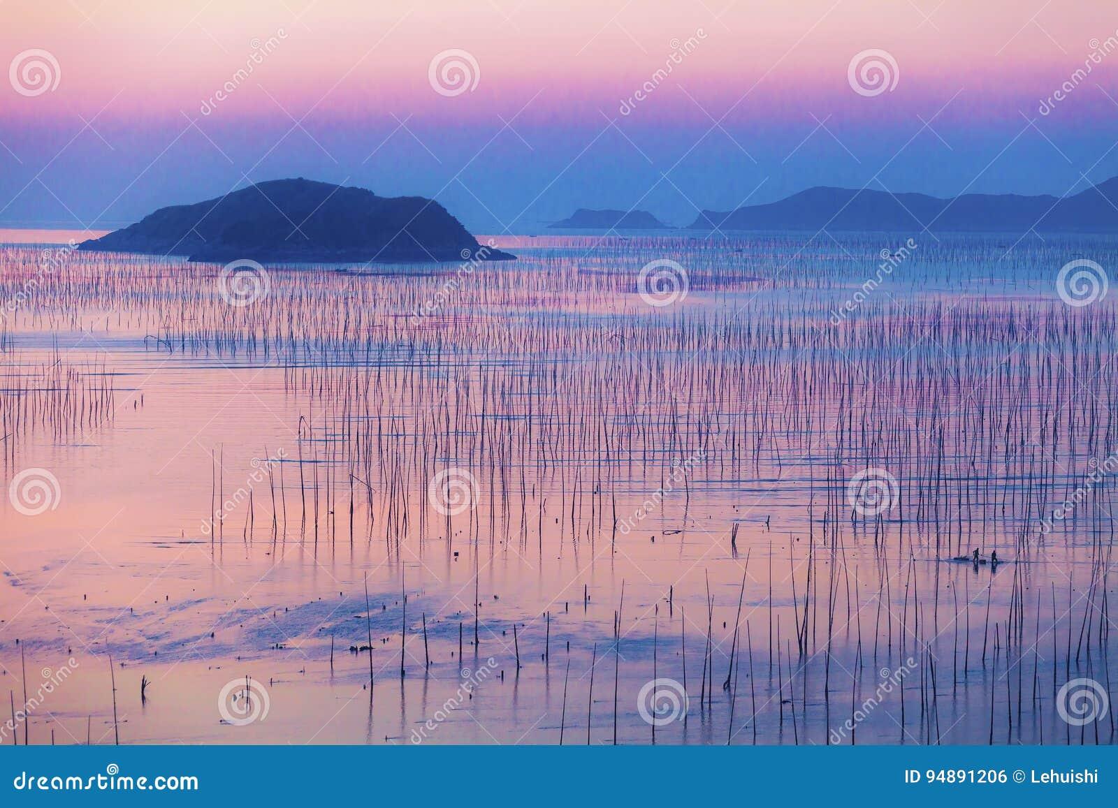 Pêcheurs et île au bord de la mer au lever de soleil