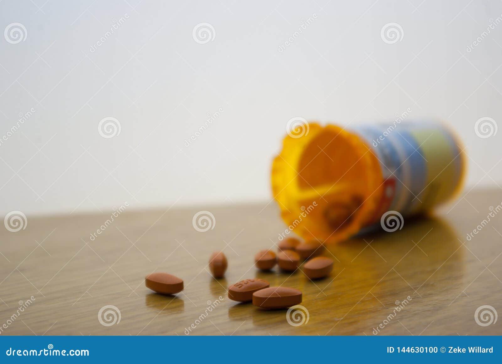 Píldoras anaranjadas derramadas en la superficie blanca