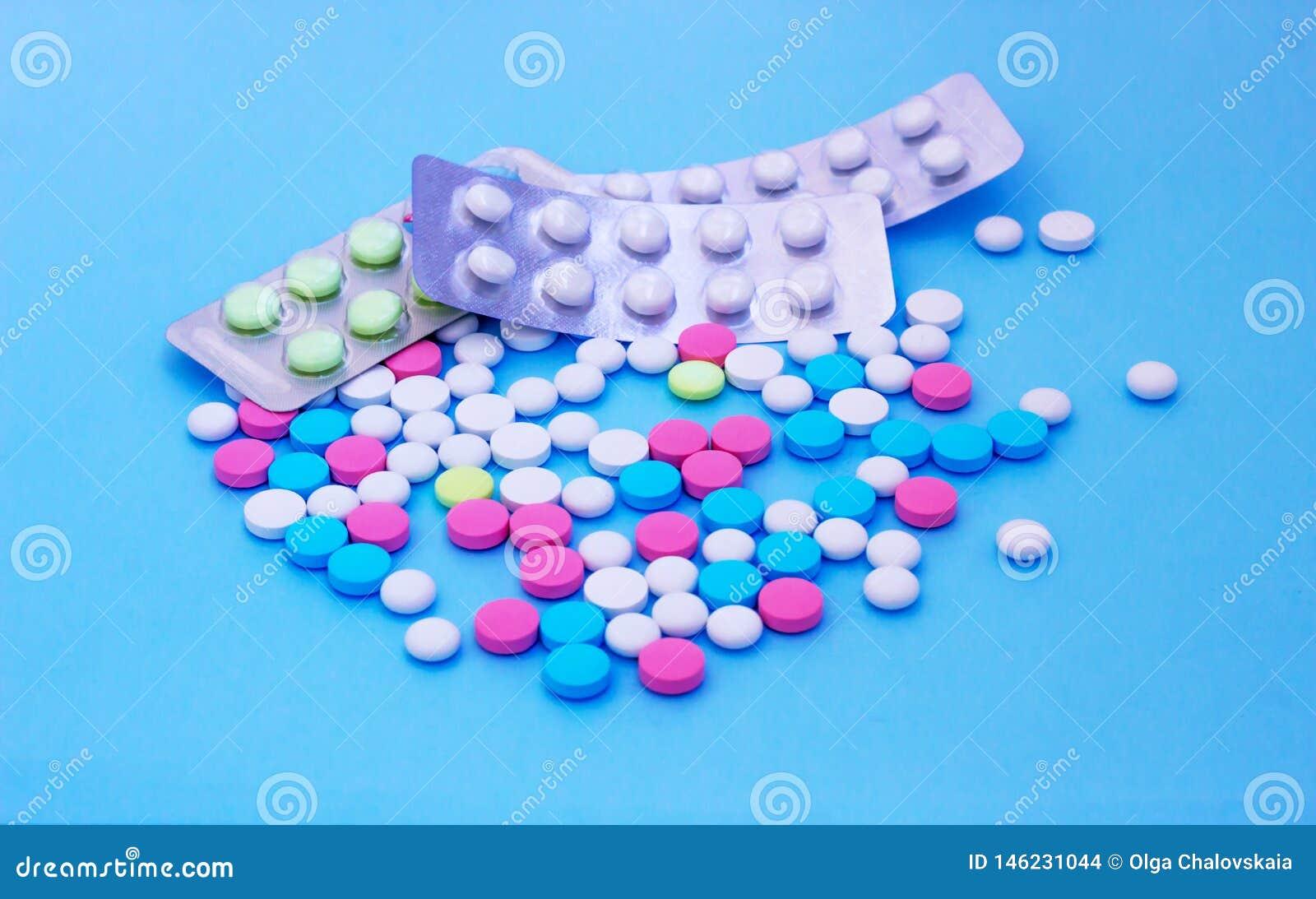 Píldoras multicoloras en fondo azul con el espacio de la copia